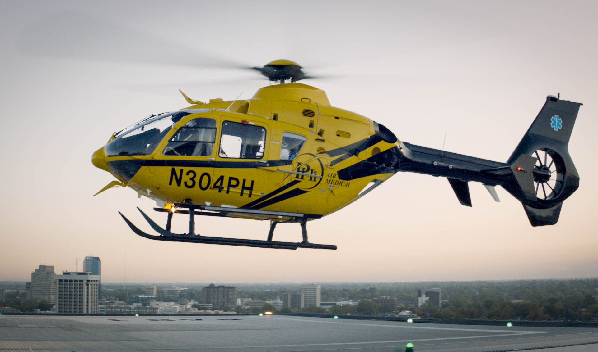 A yellow and black helicopter hovers in the sky, with the Lexington skyline in the background.