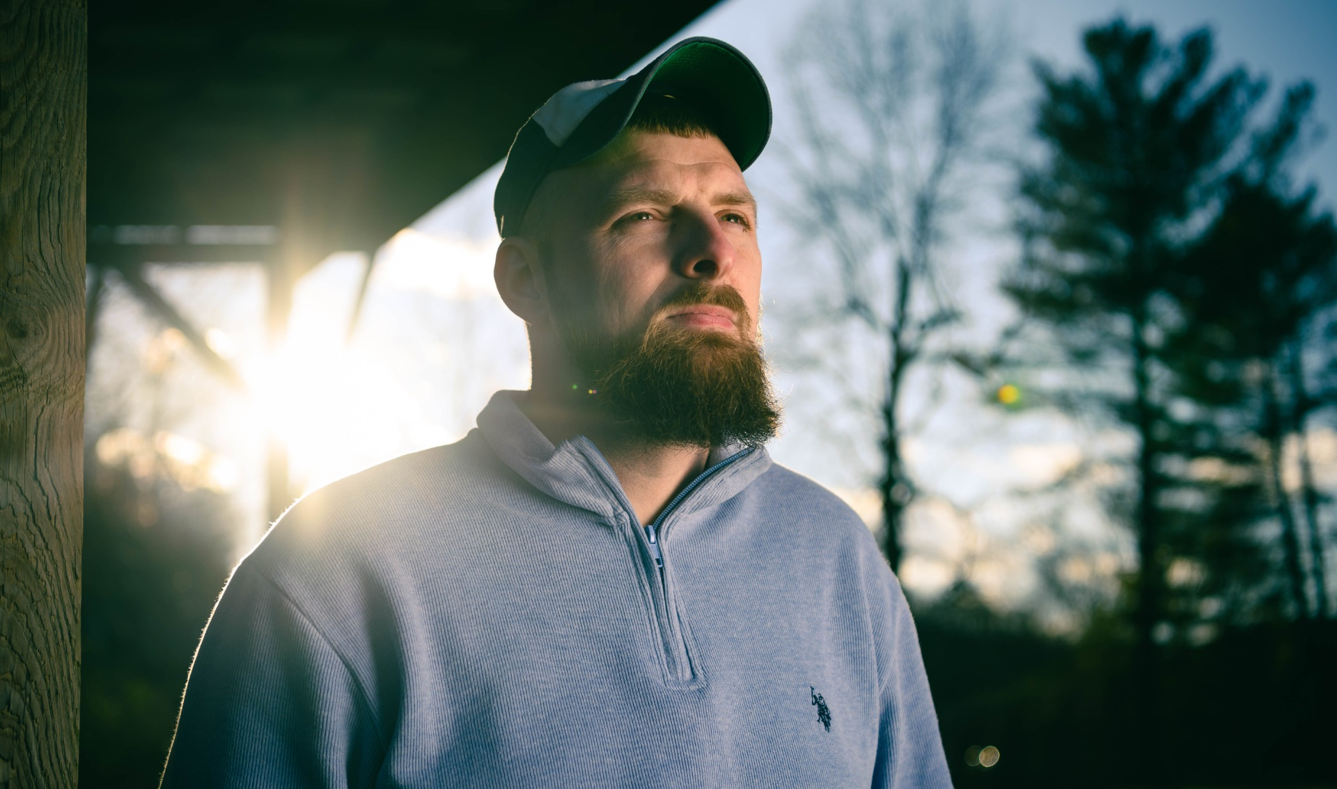 Timothy stands on his porch as the sun sets beneath the trees behind him. He is looking past the camera with a determined expression.