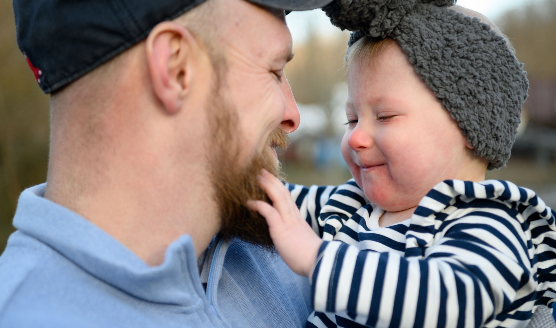 Timothy holds MaKenzie and smiles as she grins at him and touches his beard.