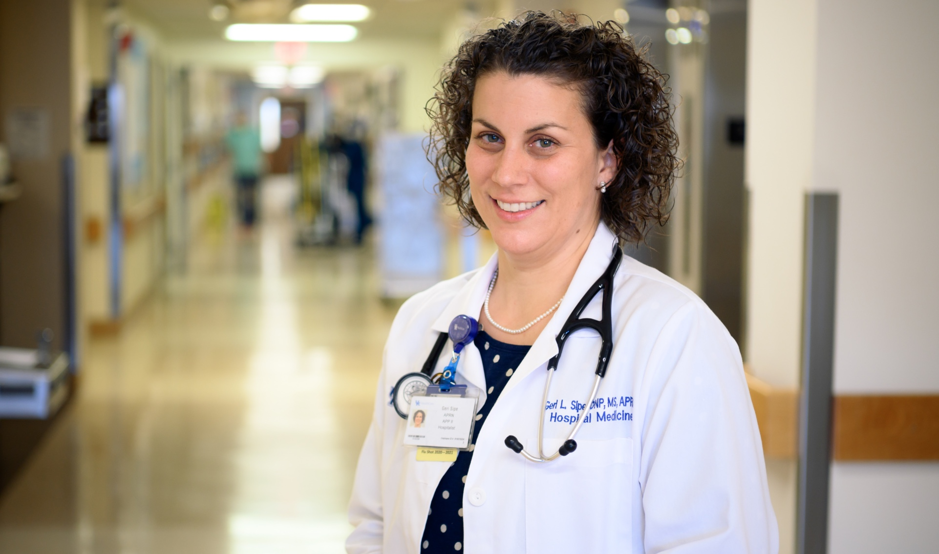 Geri stands in the hallway of the hospital. She is wearing a white coat with a stethoscope around her neck, a pearl necklace, and blue polka dot blouse.