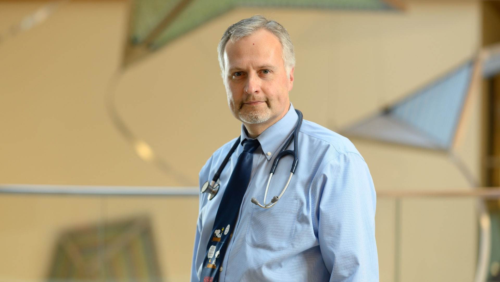 Dr. Stefan Kiessling, a middle-aged white man with grey hair, stands in the lobby of Kentucky Children's Hospital wearing a light blue shirt, with a navy-blue tie and a stethoscope placed around his neck.