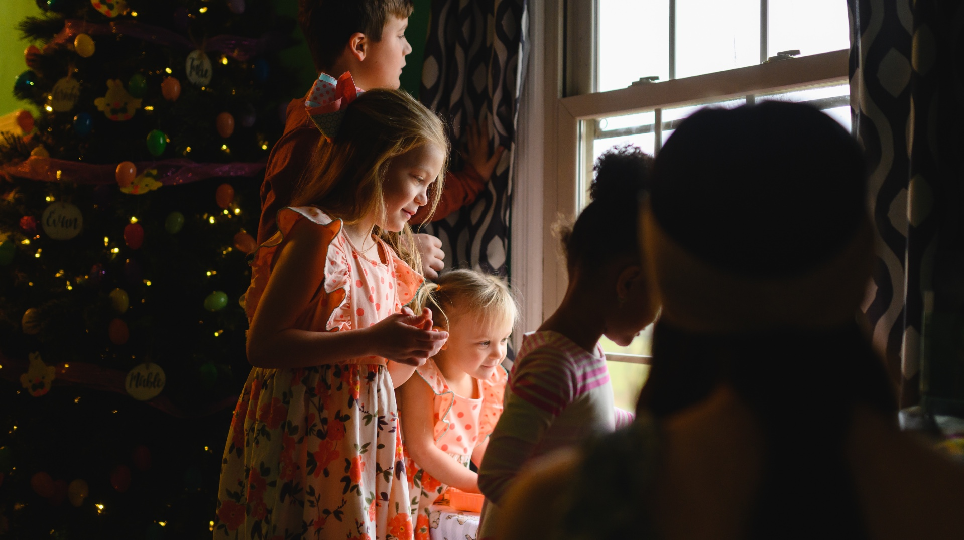 Standing next to the Christmas tree inside the house, Julie, her siblings, Jennifer and her daughter stare out the window.
