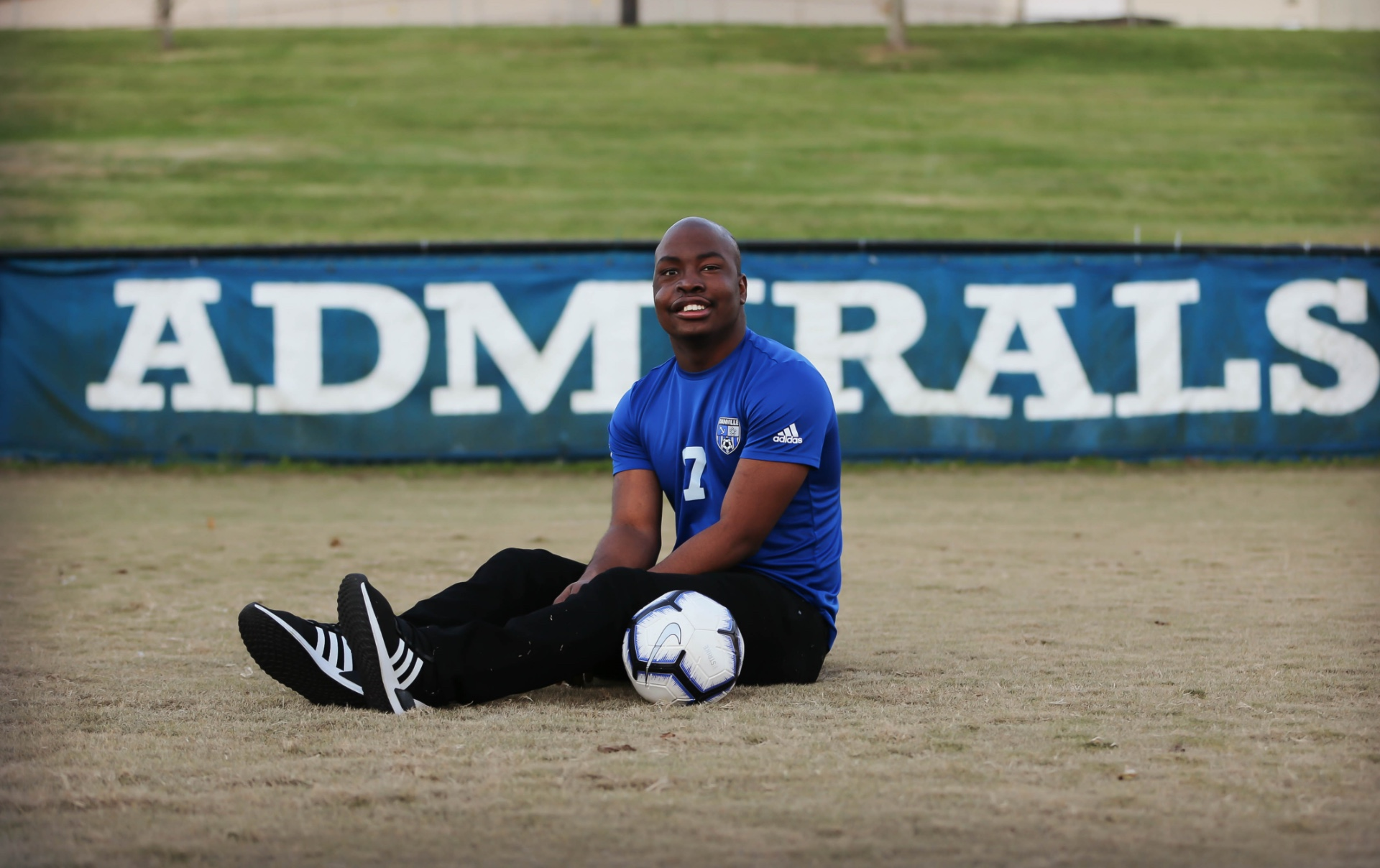 Remilson sits on the soccer field beside a soccer ball. He is wearing his blue number seven Danville soccer jersey with black pants and black and white sneakers.