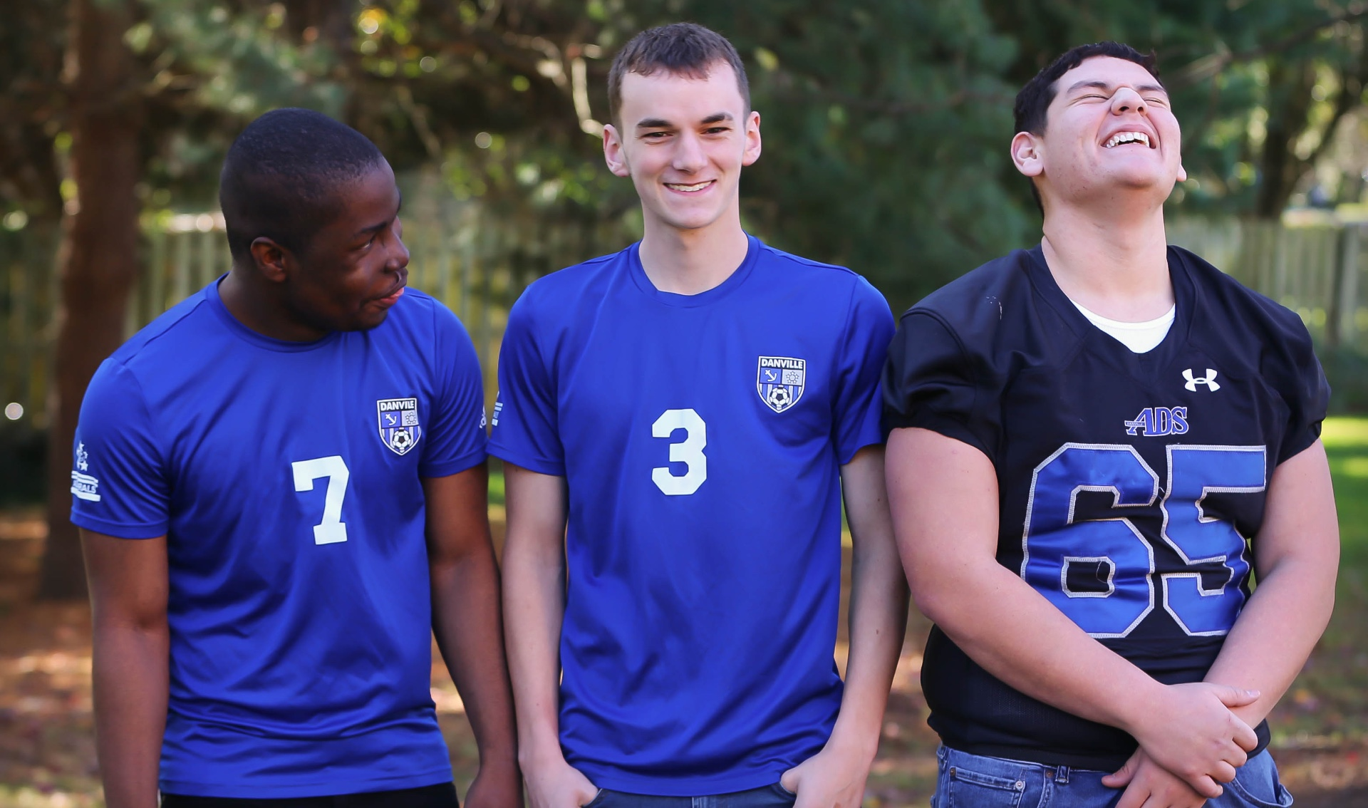 Remilson stands and laughs alongside his brother Zach, a teenage white boy with short black hair, and his brother Alex, a teenage white boy with short black hair. Zach is wearing a Danville soccer jersey similar to Remilson while Alex is wearing a navy blue football jersey.