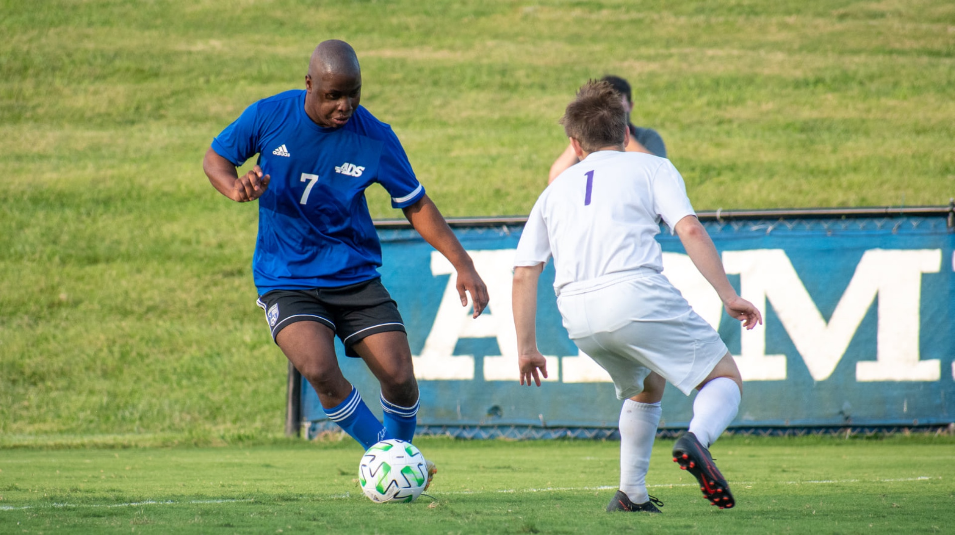 Remilson is dribbling the ball against an opponent in a soccer match. He is wearing his full Danville uniform: a blue soccer jersey and black shorts.
