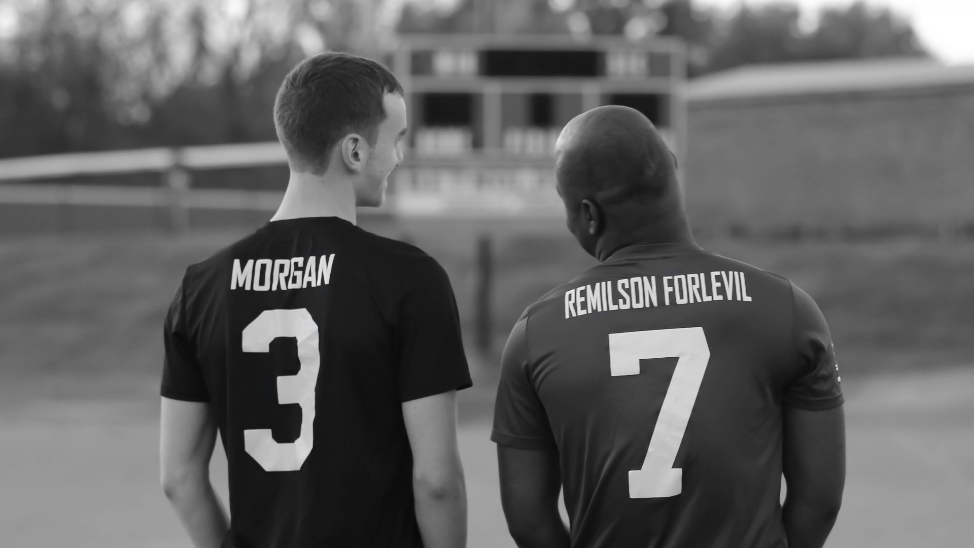 A black and white photo of Zach and Remilson, smiling and talking to each other. Their backs are to the camera and we can see the back of their soccer jerseys, with number three (Zach) and number seven (Remilson).