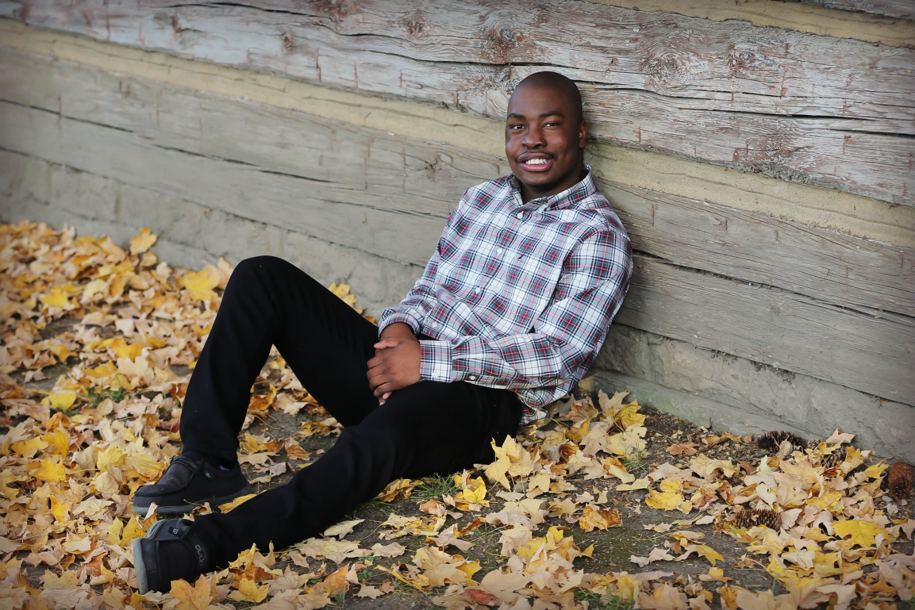 Remilson Forlevil, a teenage Black boy with very short black hair, is smiling as he sits on the ground surrounded by autumn leaves. He is wearing a grey, black and red flannel shirt with black pants and black shoes.