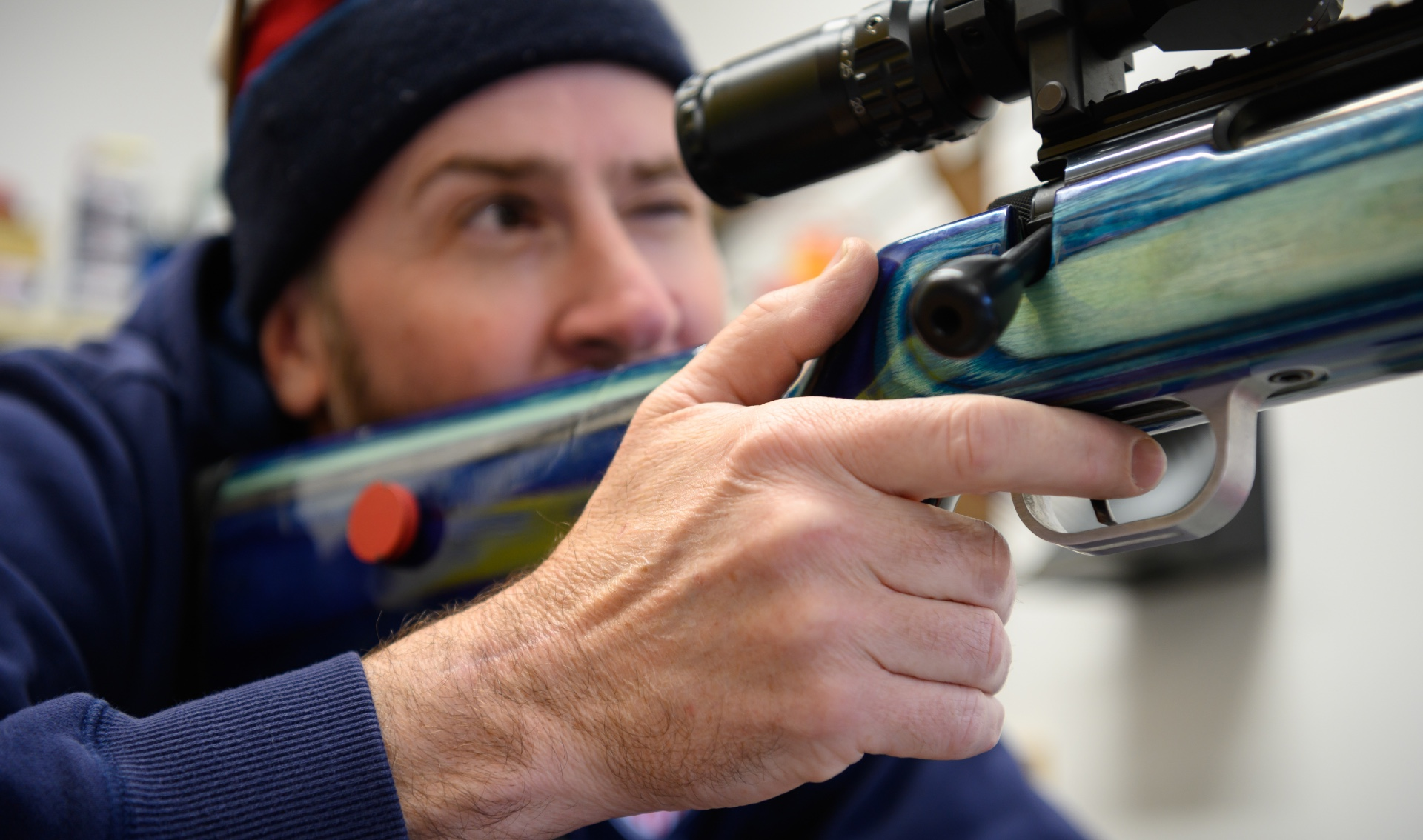 With his finger on the trigger, Addison looks through the rifle's scope