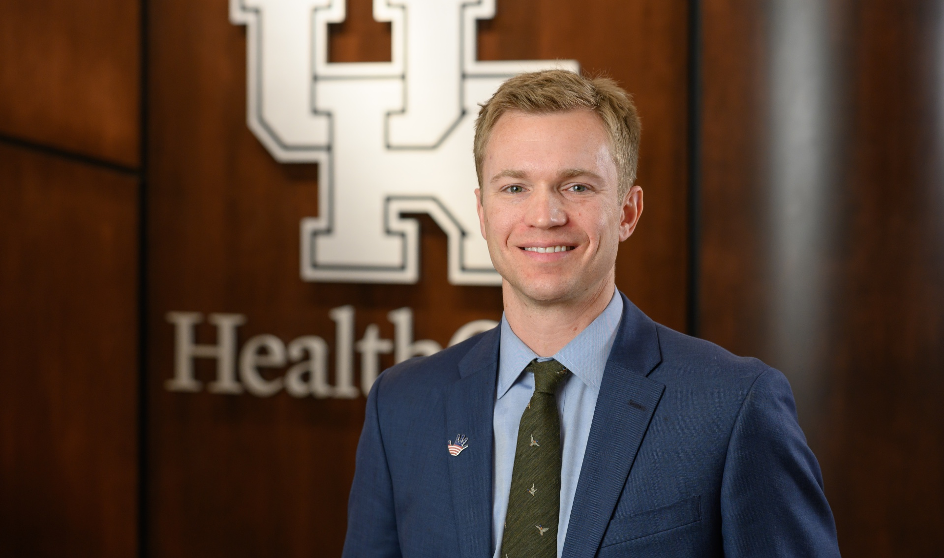 Dr. Kluemper, an adult white man with blonde hair, smiles in front of a UK HealthCare logo. He is wearing a navy suit and a green tie.