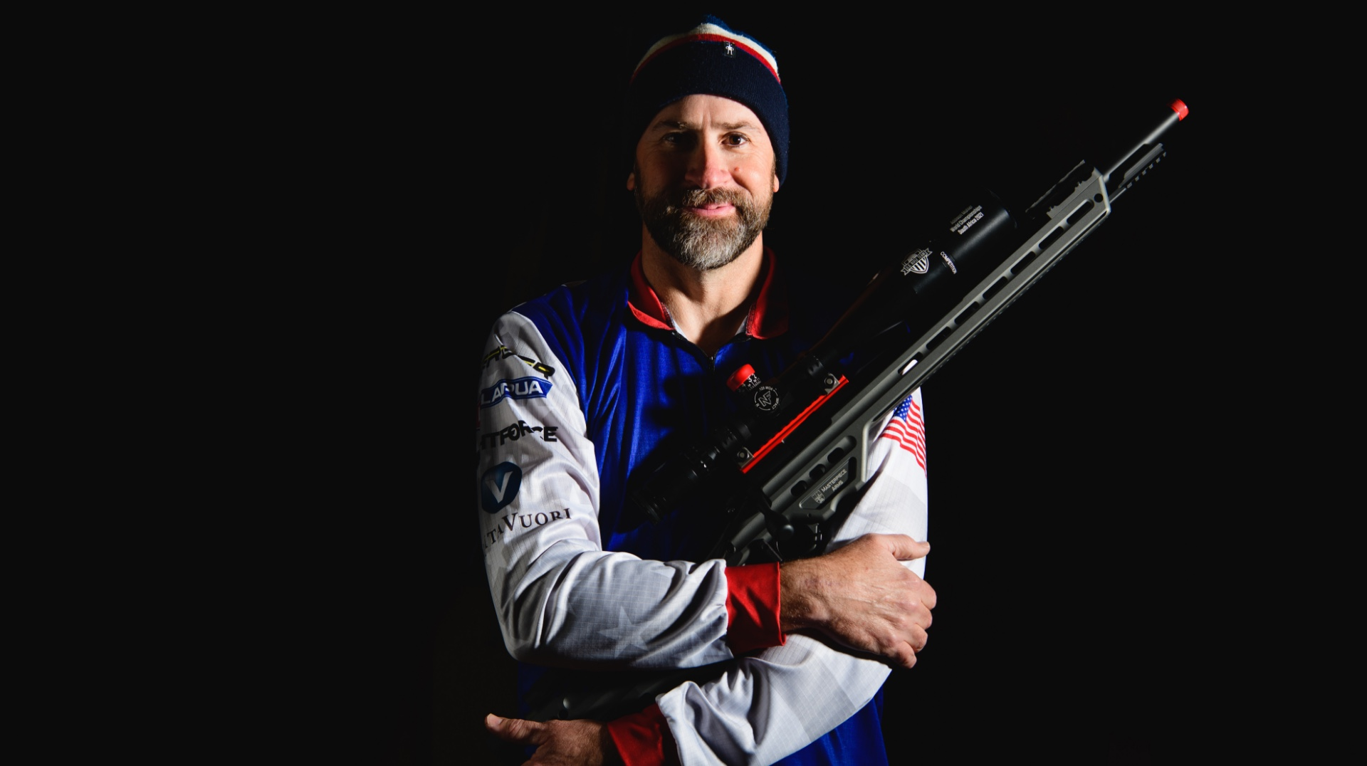 Addison stands with both hands across his chest as he holds up his rifle in his arms and smiles.
