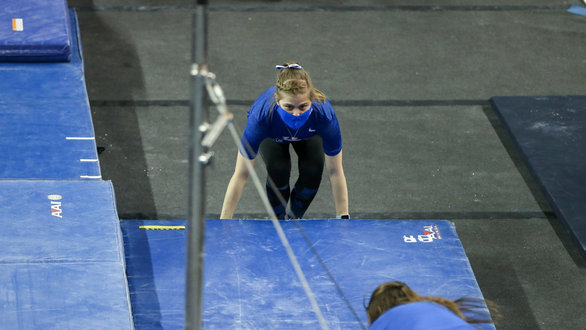 Allison squats to position a mat in place at a gymnastics practice. She is wearing a blue facemask, blue tee shirt, and black leggings. Her hair is pulled back and has a French braid across the front.