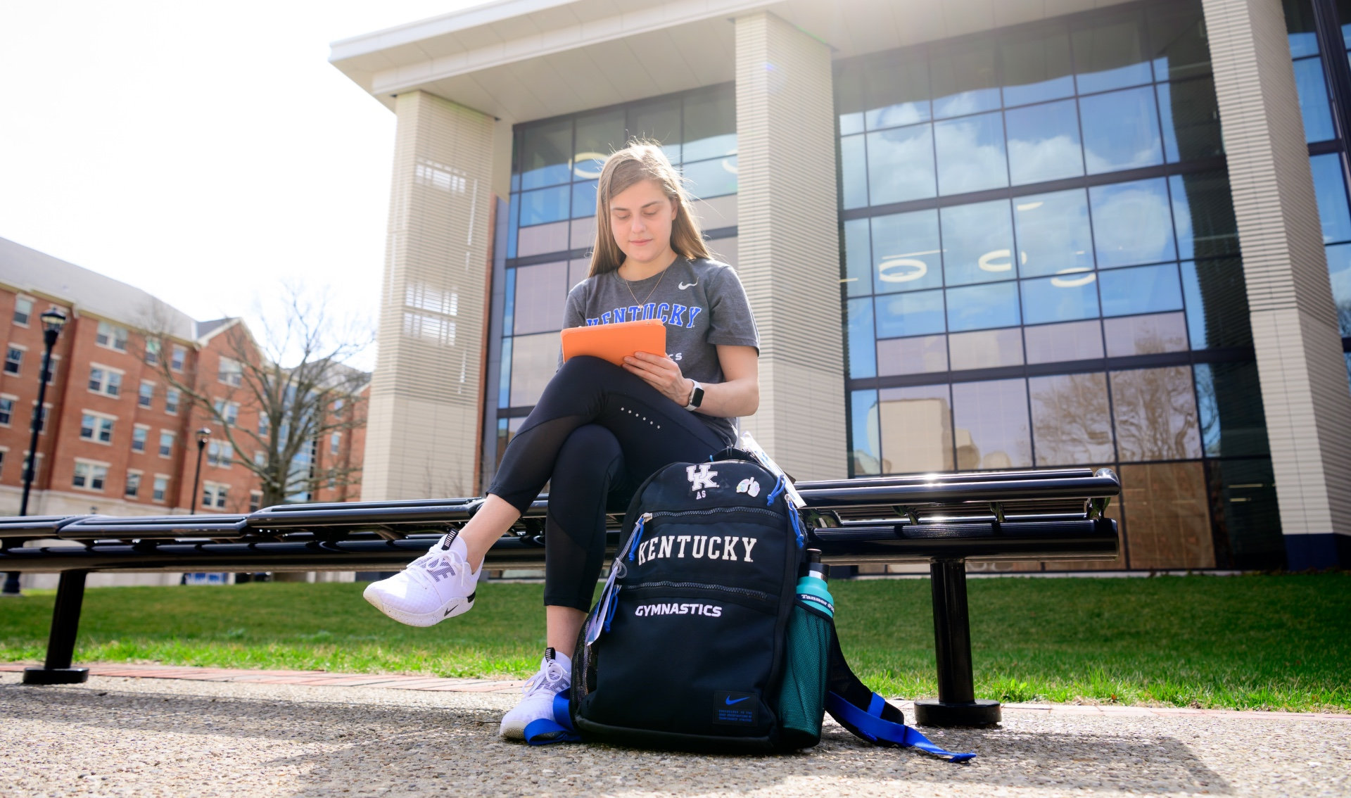 Allison sits on the bench outside the library, with her backpack on the ground beside her. She is looking at an iPad in an orange case.