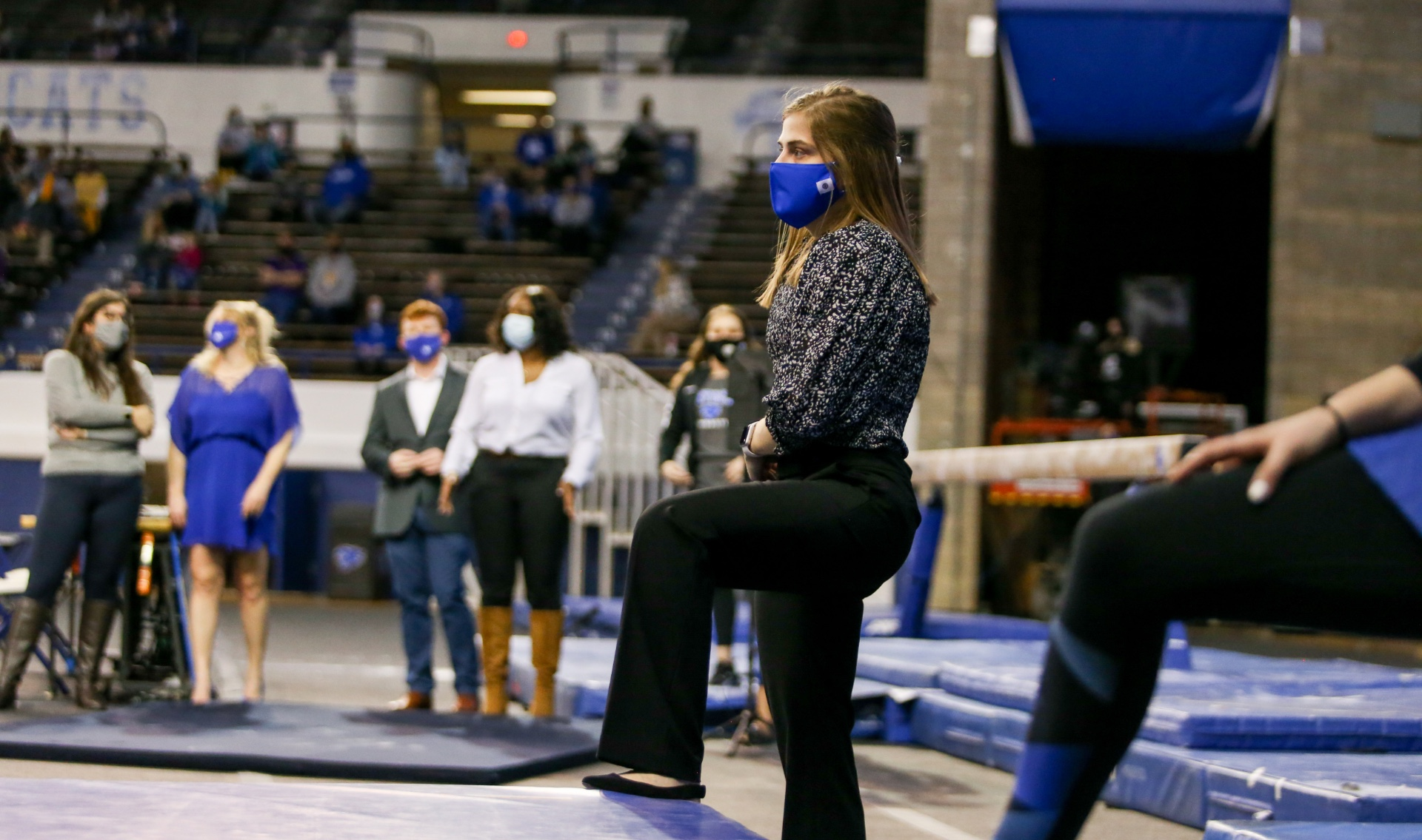 In a black and white blouse, black slacks, and a blue facemask, Allison stands at the edge of a competition space and watches her gymnastics team compete.