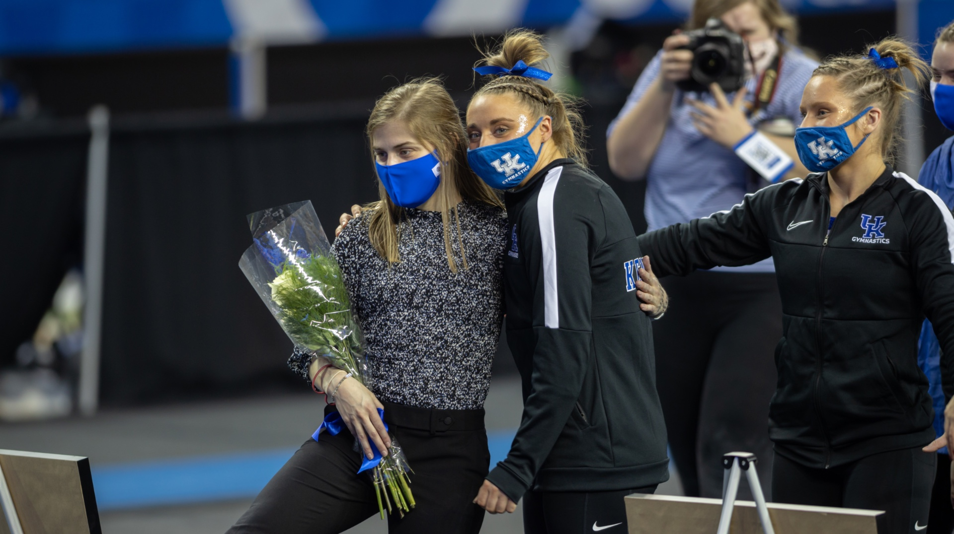 Allison poses for a photo with a fellow gymnastics teammate. They have their arms around each other. Allison is holding a bouquet of flowers. Both are wearing blue facemasks.
