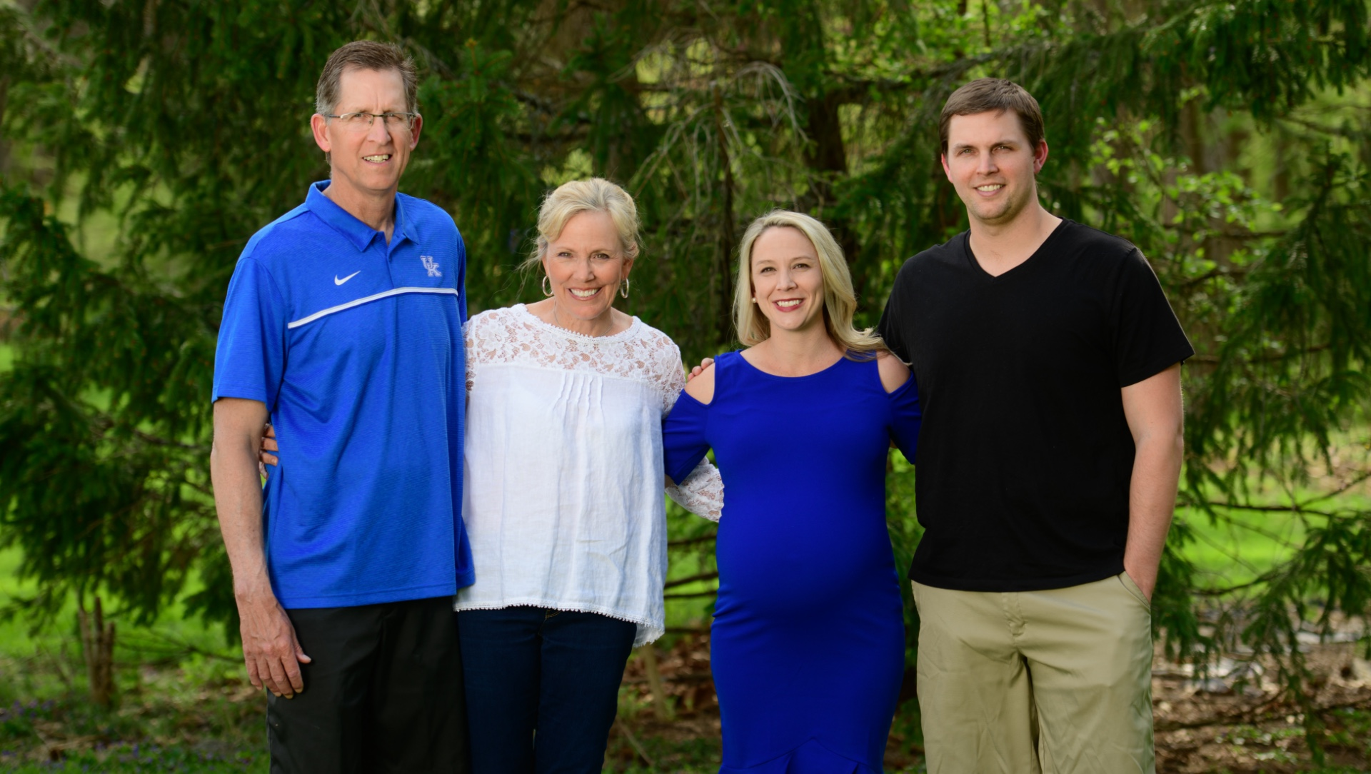 Coach O'Connor and her family gather around to take a picture outside. Beside her is her brother, Trent Martin, a white male in a black shirt; her mother, Donna Martin, an older white woman with blonde hair, wearing a white blouse; and her father, an older white man wearing a blue UK shirt.