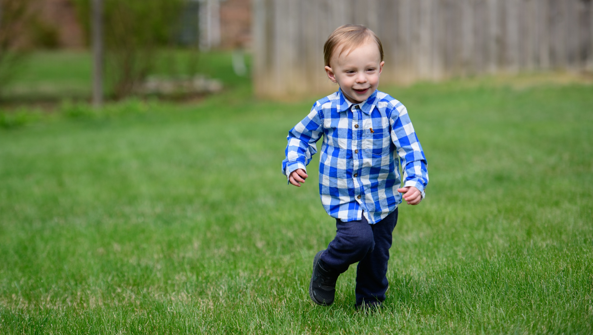 Michael runs across an open field. He is wearing a blue and white checkered shirt with navy blue pants.
