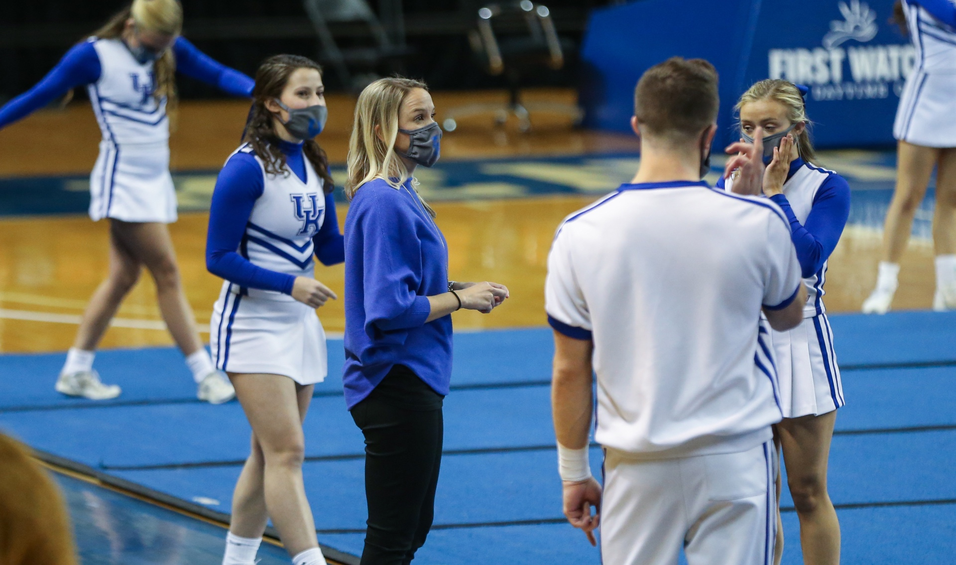Coach O'Connor stands around her male and female cheerleading student athletes as they practice. All of them are wearing face masks.