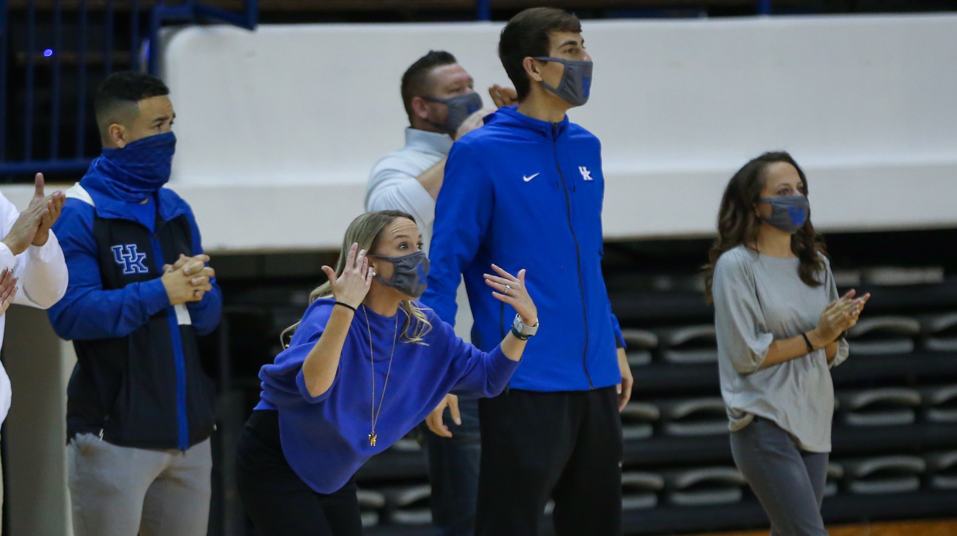 With her hands up in the air, Coach O'Connor passionately cheers and directs her team from the sidelines at a competition.