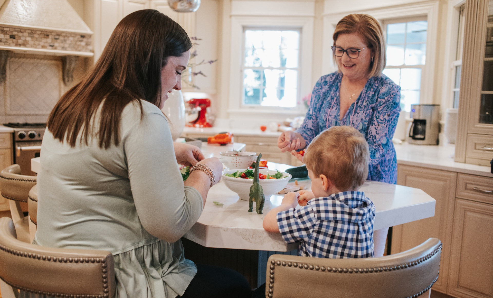 Nancy Johnson, an older white woman with blonde hair wearing a blue and pink print top, preps vegetables in her kitchen. With her is her grandson, a toddler in a blue, white and black checkered shirt, and her daughter, Kelsey, a younger white woman with brown hair, wearing a light green top.