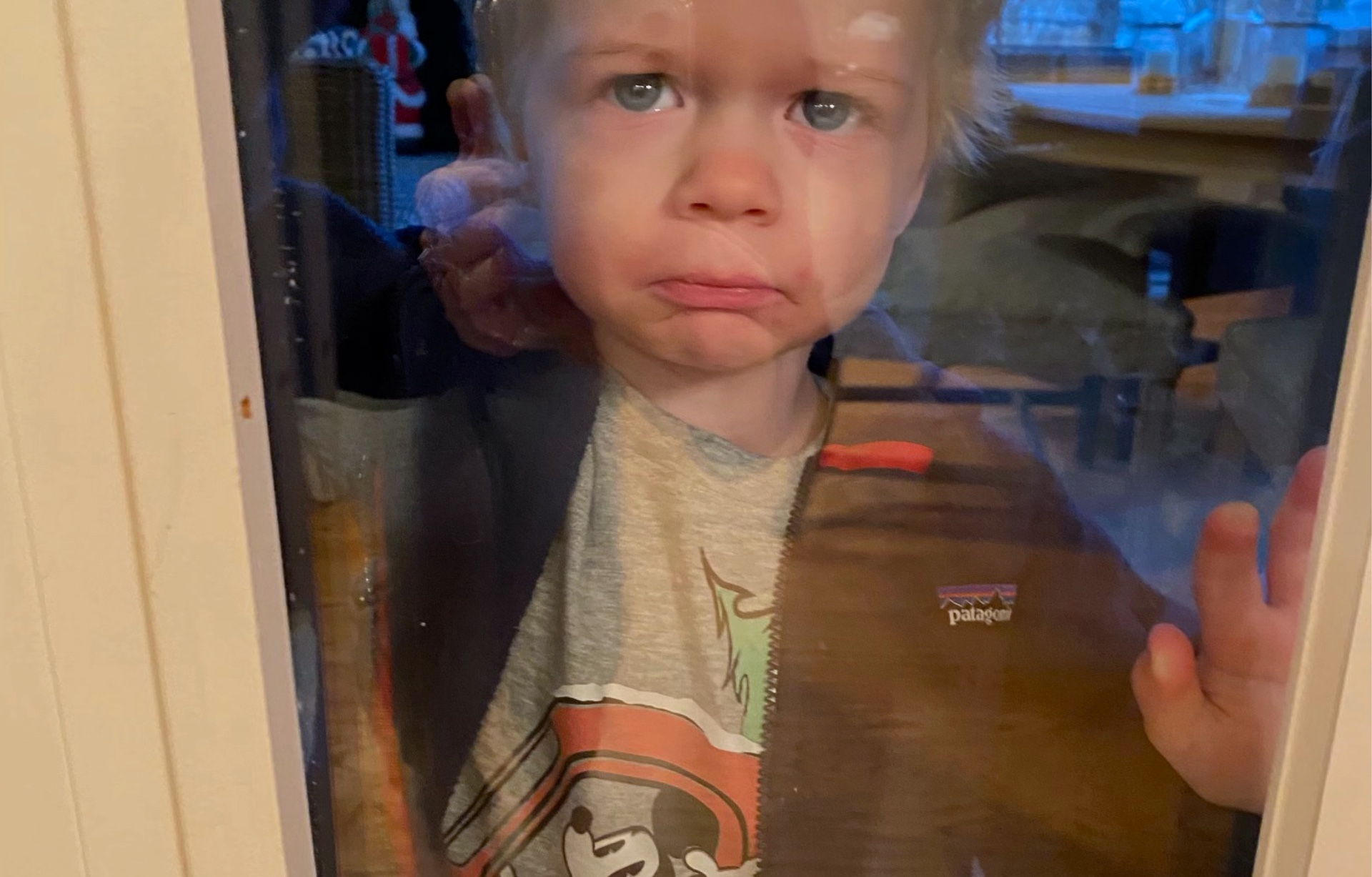 Kelsey's two-year-old stands on the other side of a window, frowning with a teary-eyed expression.