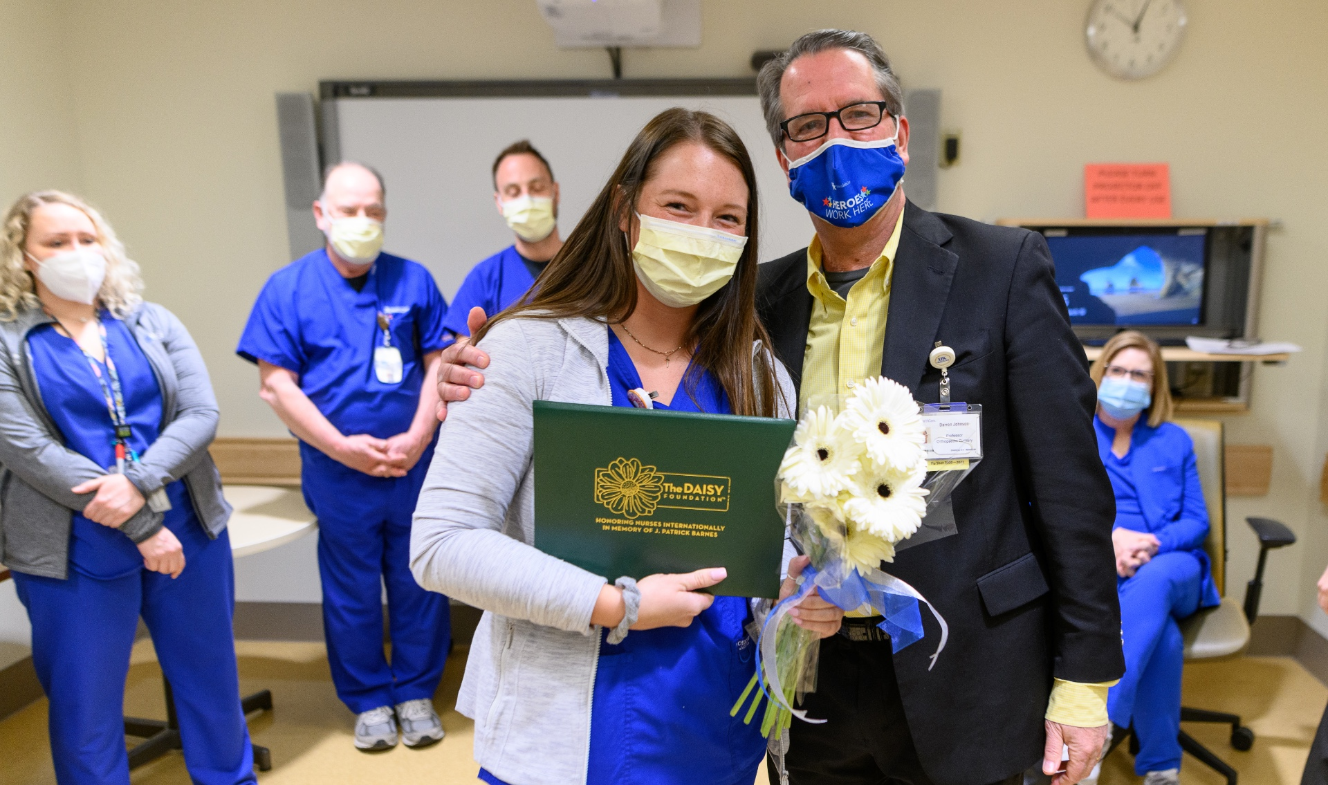 Holding a bouquet of flowers, Alexis Zody, an adult white woman with brown hair in blue scrubs, stands beside Dr. Johnson for a photograph. They are surrounded by colleagues, and everyone pictured is wearing a facemask.