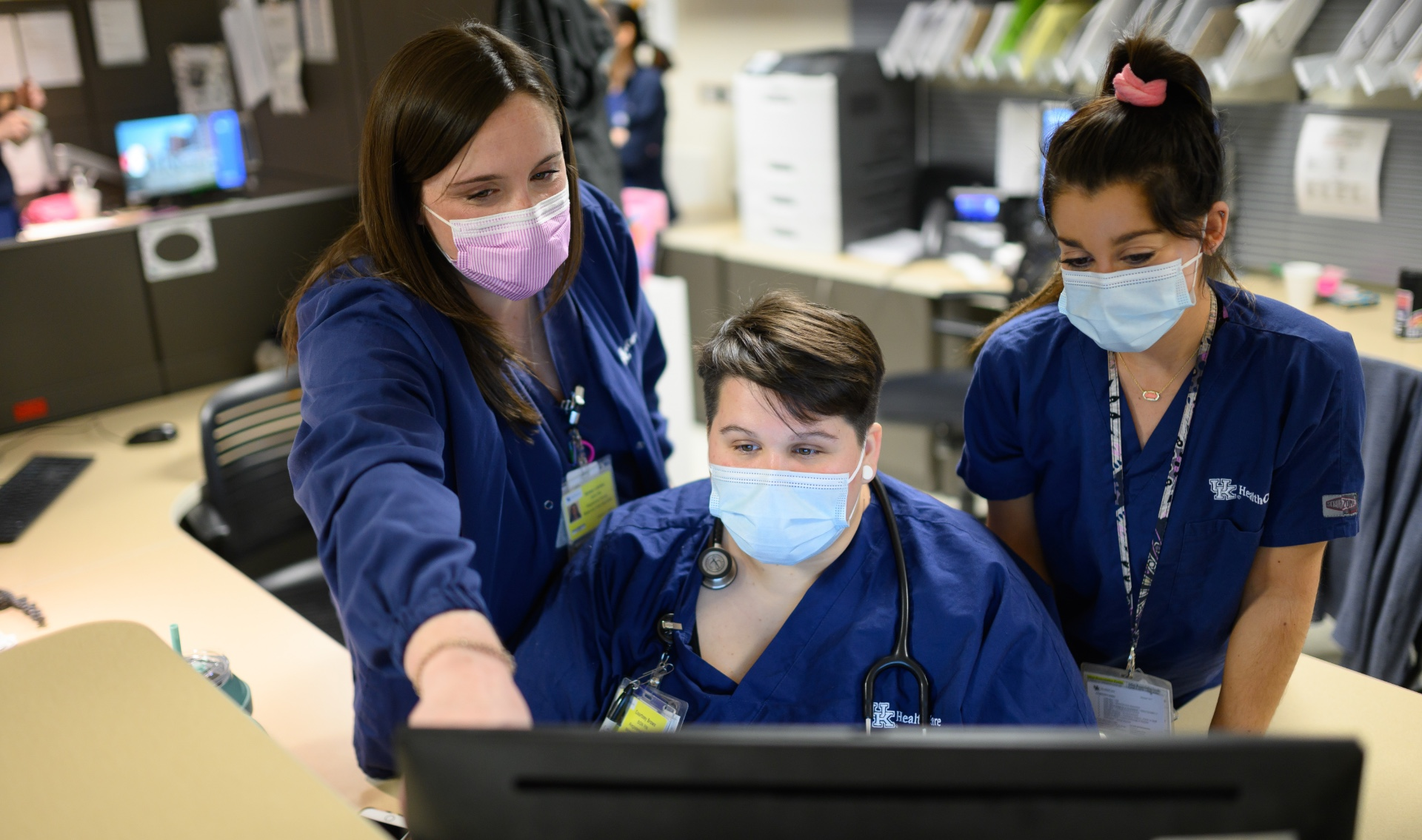 Kelsey stands beside two of her female work colleagues pointing to a computer screen. They are all wearing navy scrubs with different colored face masks.