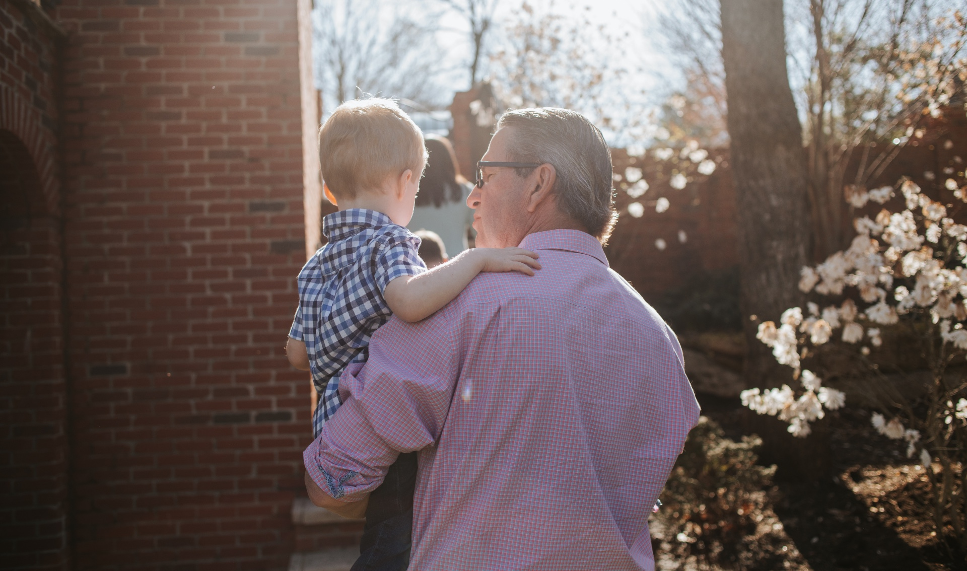 Using one arm, Dr. Johnson carries his grandson outside.