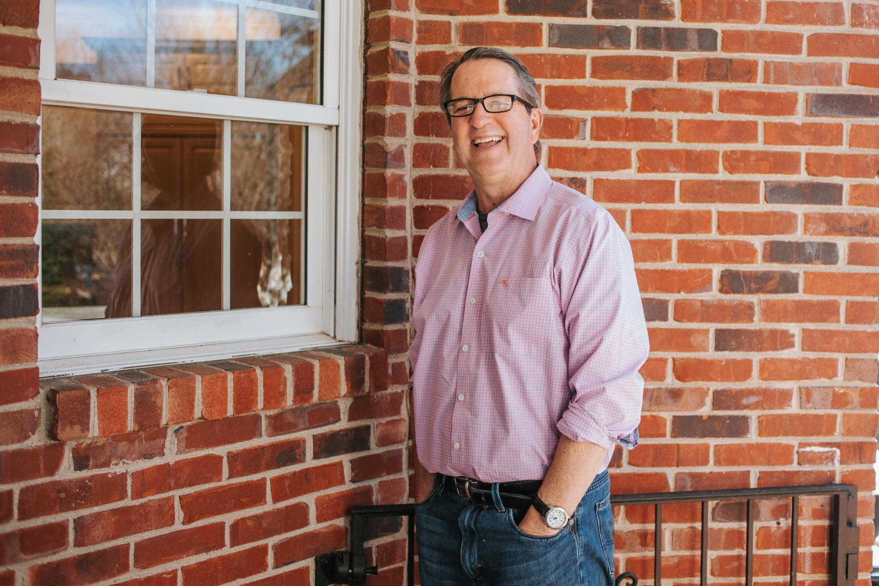 Dr. Darren Johnson, an older white man with black and grey hair, stands outside in front of a brick wall. He is wearing a light pink checkered shirt, blue jeans and black spectacles.