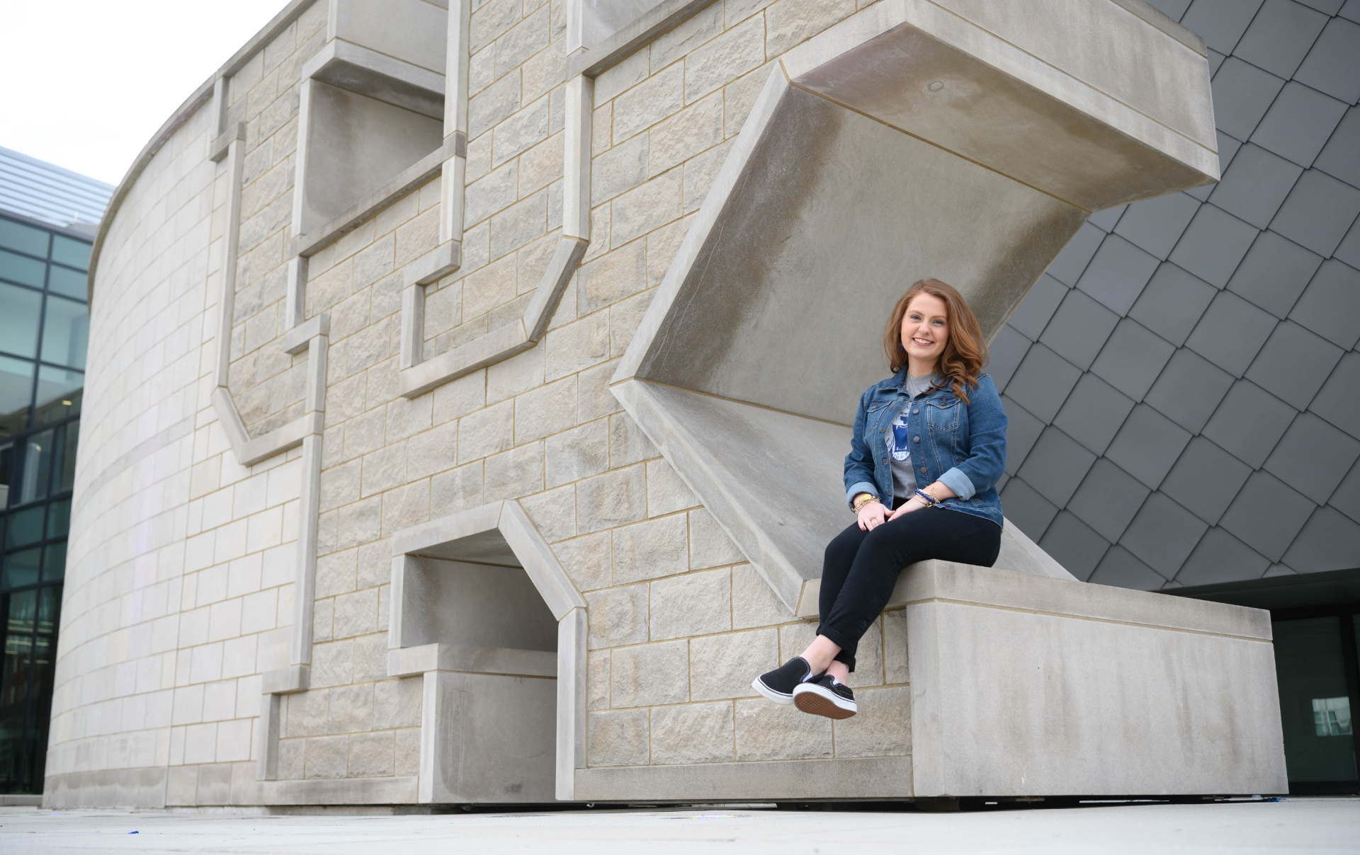 Fielden smiles at the camera as she sits on a giant sculpture of the UK logo outside the student center.