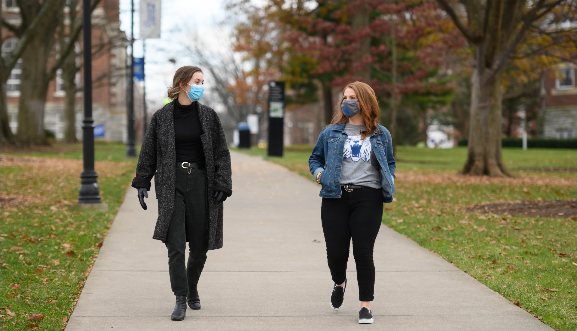 Fielden and another college student smile at each other as they walk down a path on UK's campus. Both are wearing masks.
