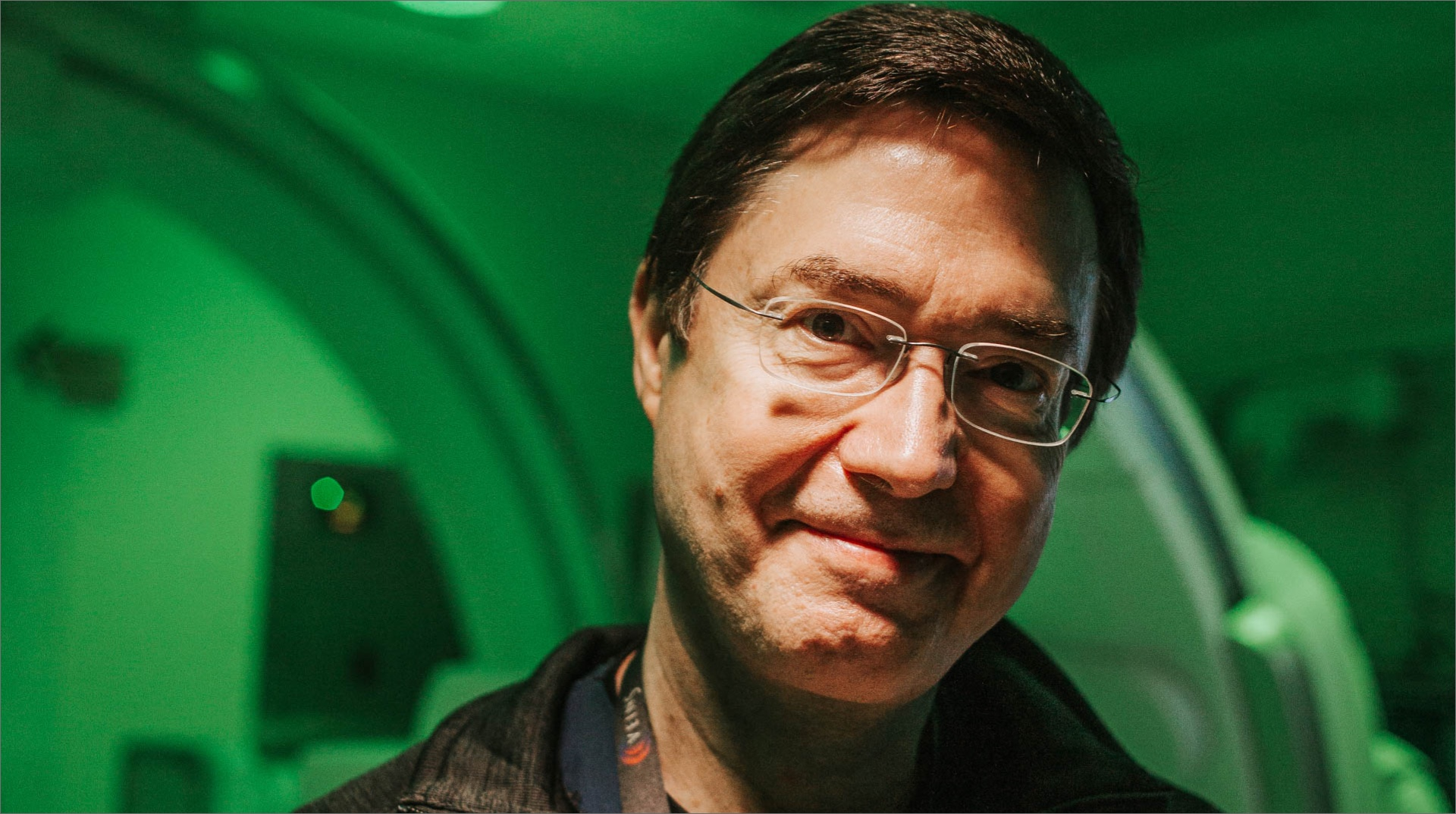 A portrait of Dr. Gurley, a middle-aged white man with dark hair and glasses. He is smiling slightly and standing in a medical setting, which is cast in a green light.