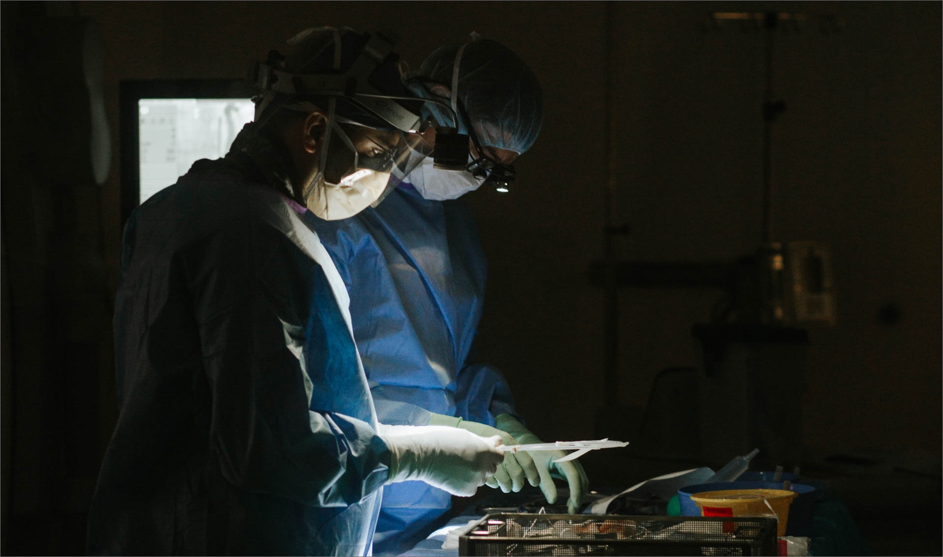 Two surgeons gather their tools for surgery. Both are wearing scrubs, masks, goggles, and gloves. The photo is dark, with dramatic lighting on their tools.