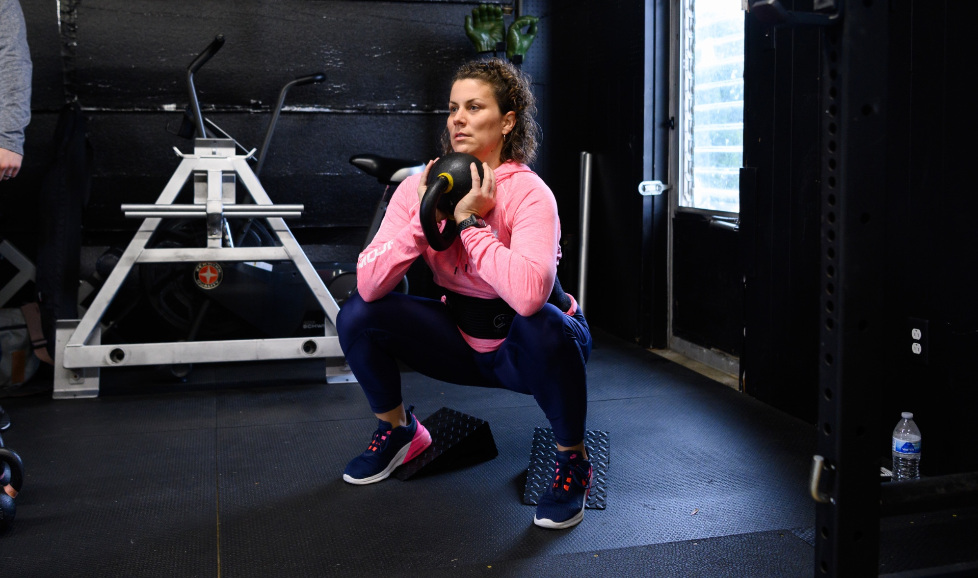 Geri looks focused as she squats holding a kettlebell while working out in the gym.