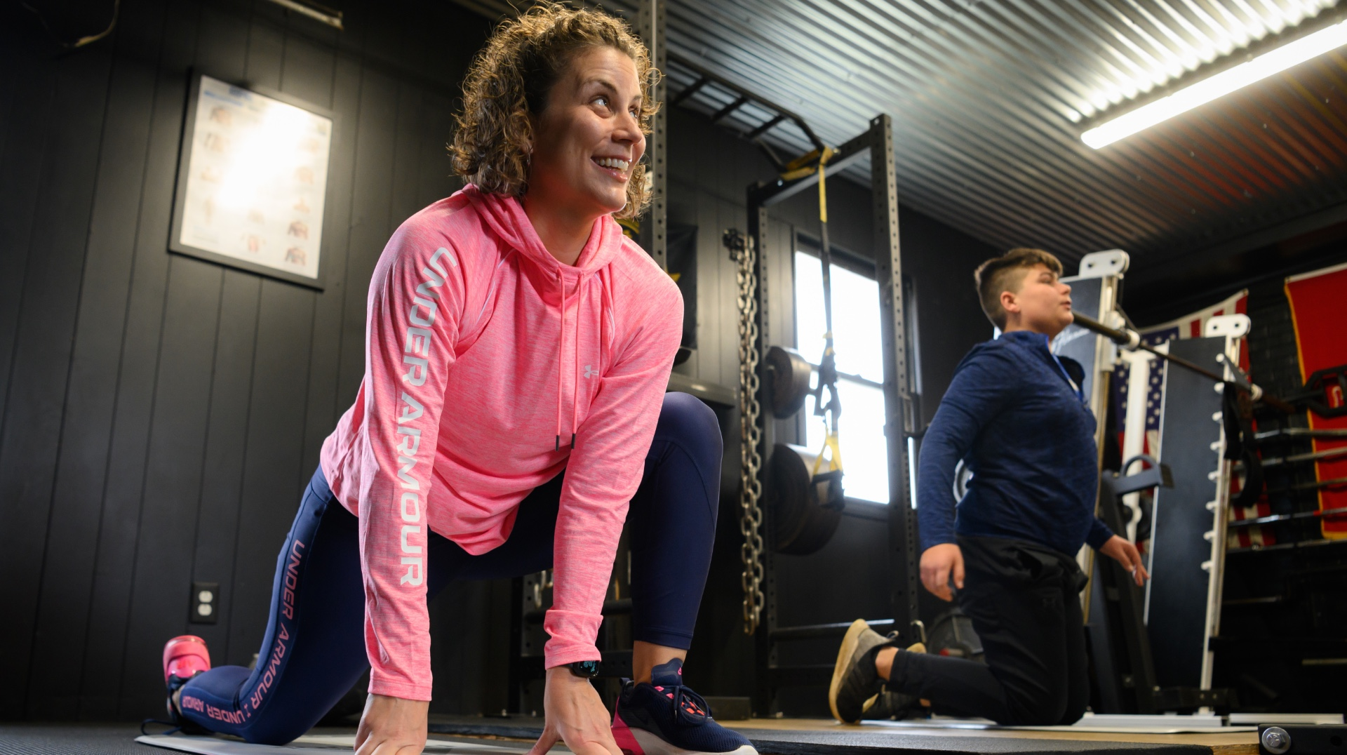 Geri smiles as she works out in the gym next to her son. She is doing a lunge and looking off-camera.