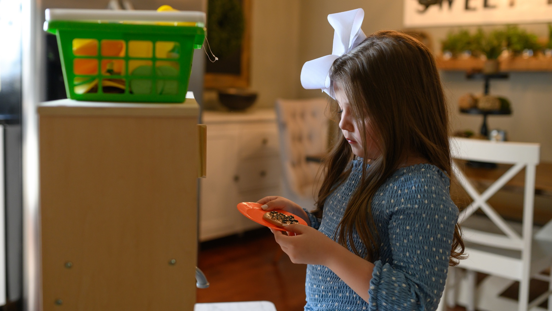 Henley stands in a play kitchen looking down at a cookie on an orange plate that she is holding.