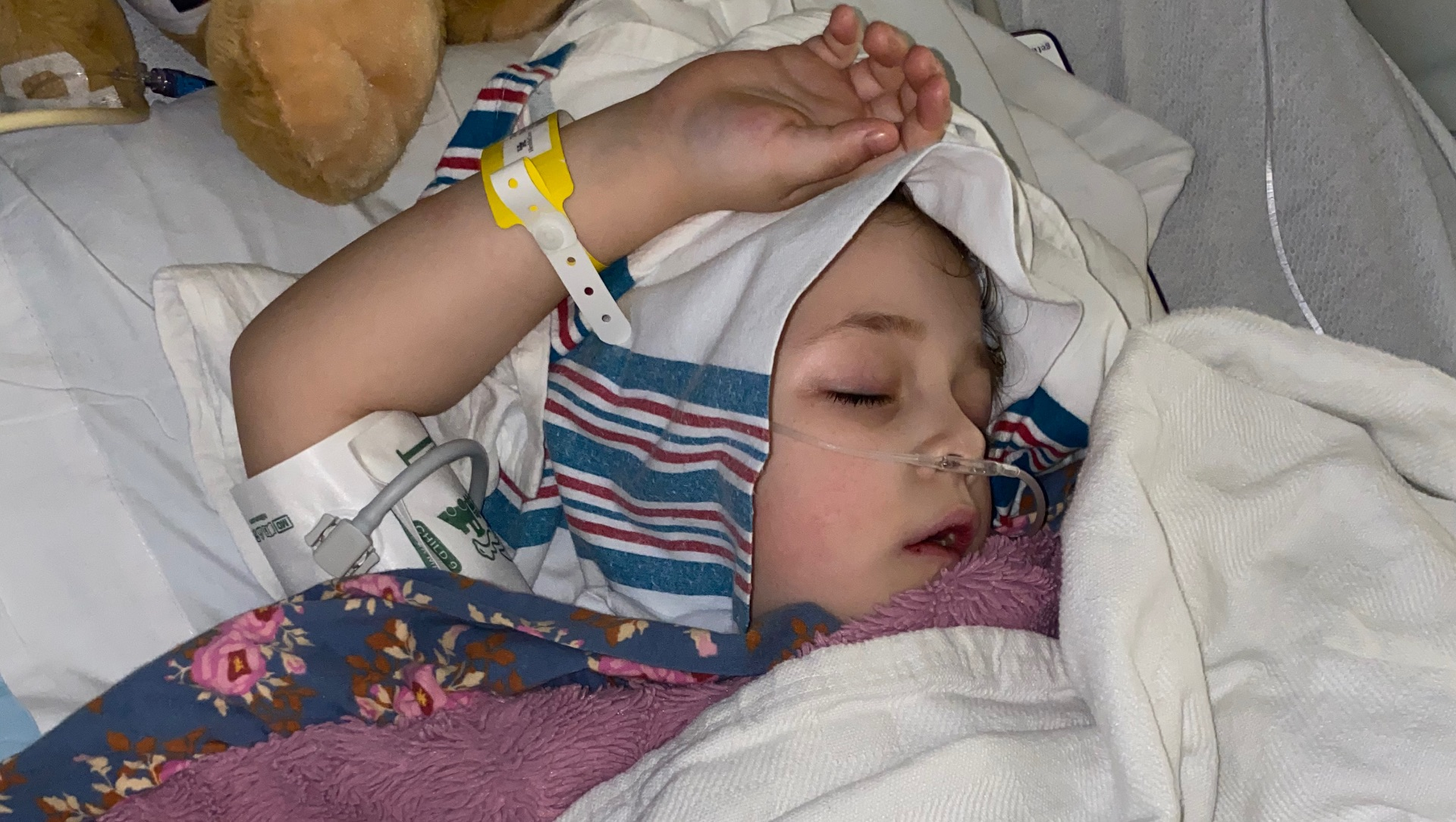 With an oxygen tube connected to her nose, her hand resting on her head, and a cloth over her head, Henley sleeps in a hospital bed.