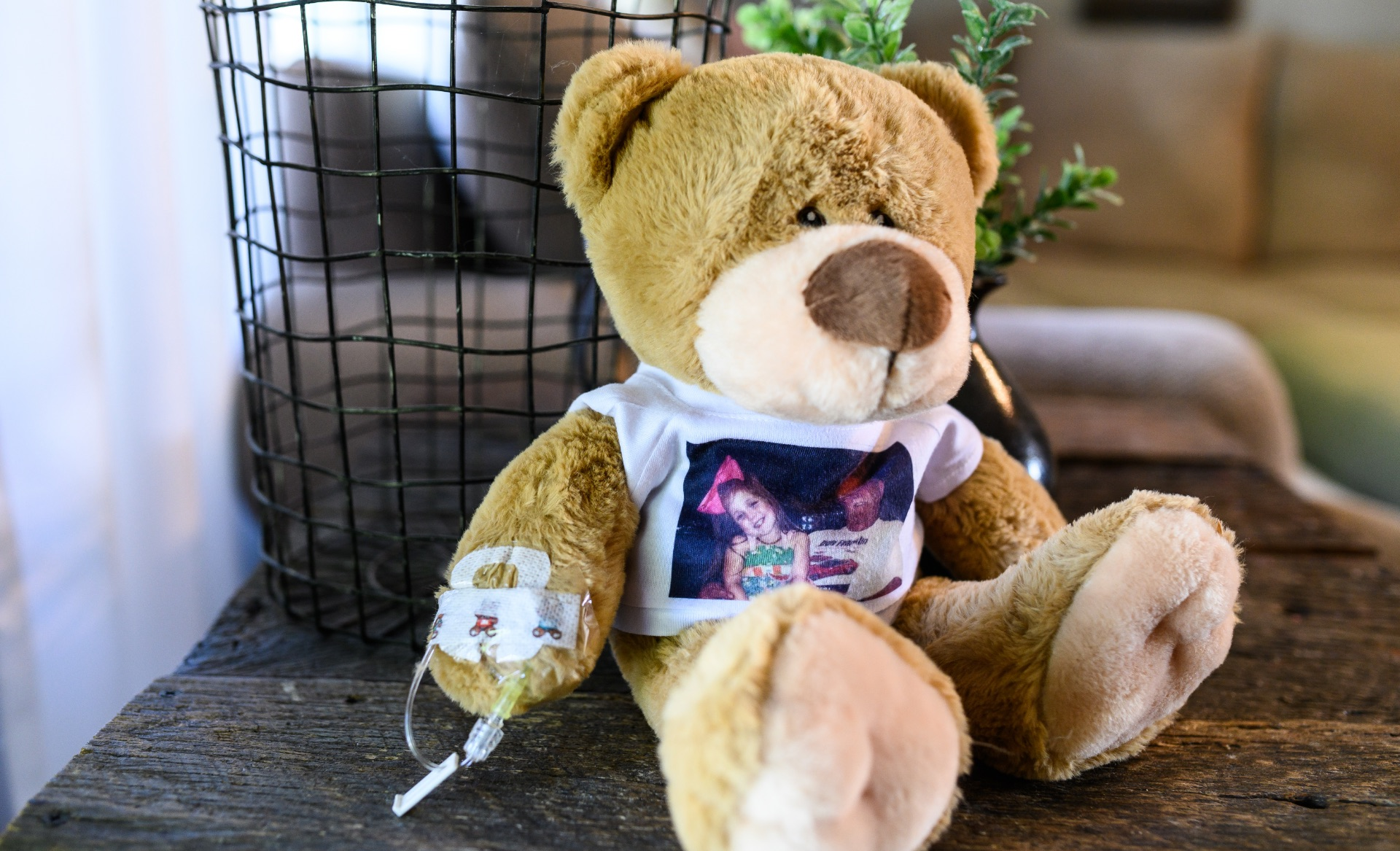 Henley's teddy bear Donnie, a brown stuffed bear wearing a white shirt with a picture of Henley and her grandfather printed on it. Donnie has an IV connected to one of his arms.