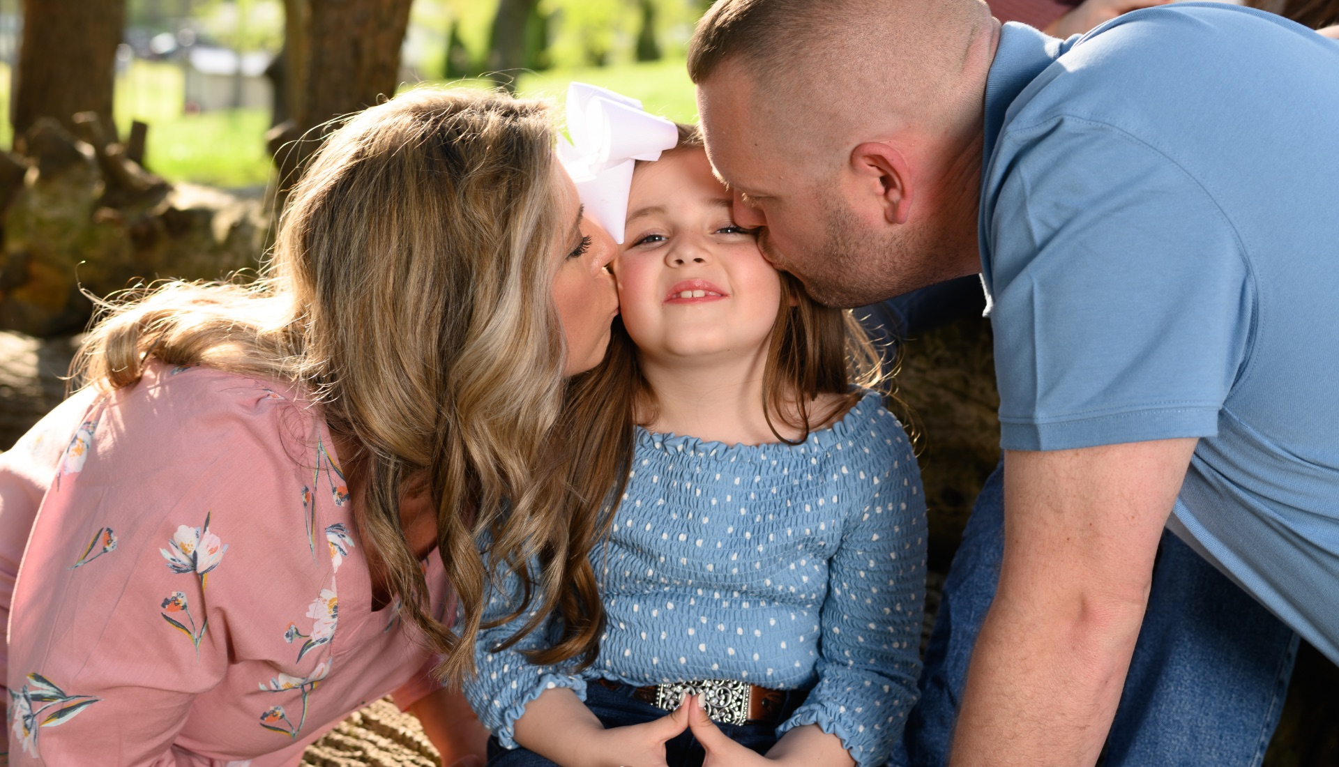 Henley smiles as she sits in between her mom, Lindsay, a middle-aged white woman with blonde hair, wearing a pink top, and her father, Jarred, a middle-aged white man with short brown hair, wearing a blue shirt. They kiss either side of her cheeks.