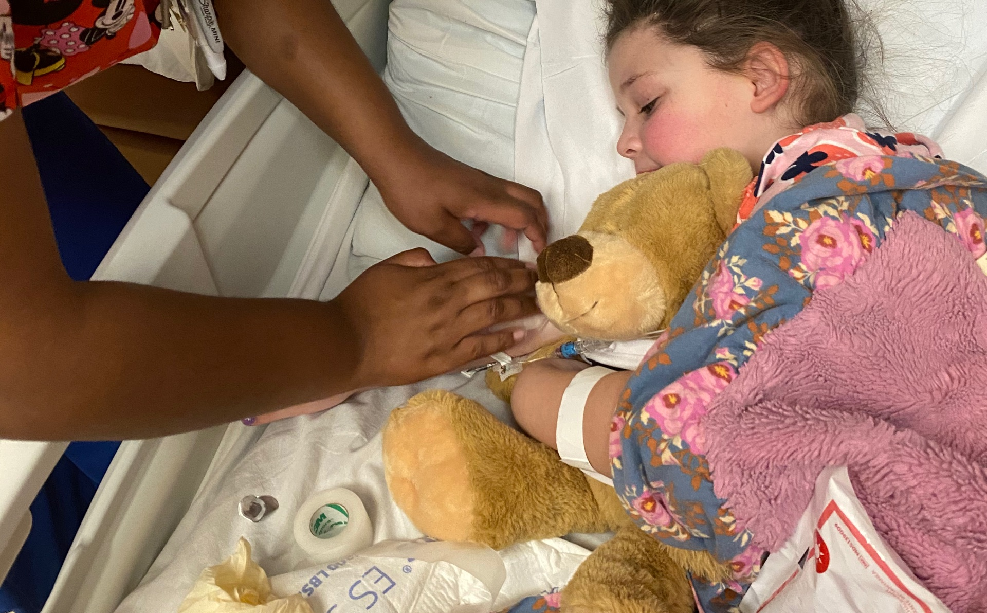 Henley and Donnie snuggle in a hospital bed covered by blankets as a nurse checks on Henley's IV.