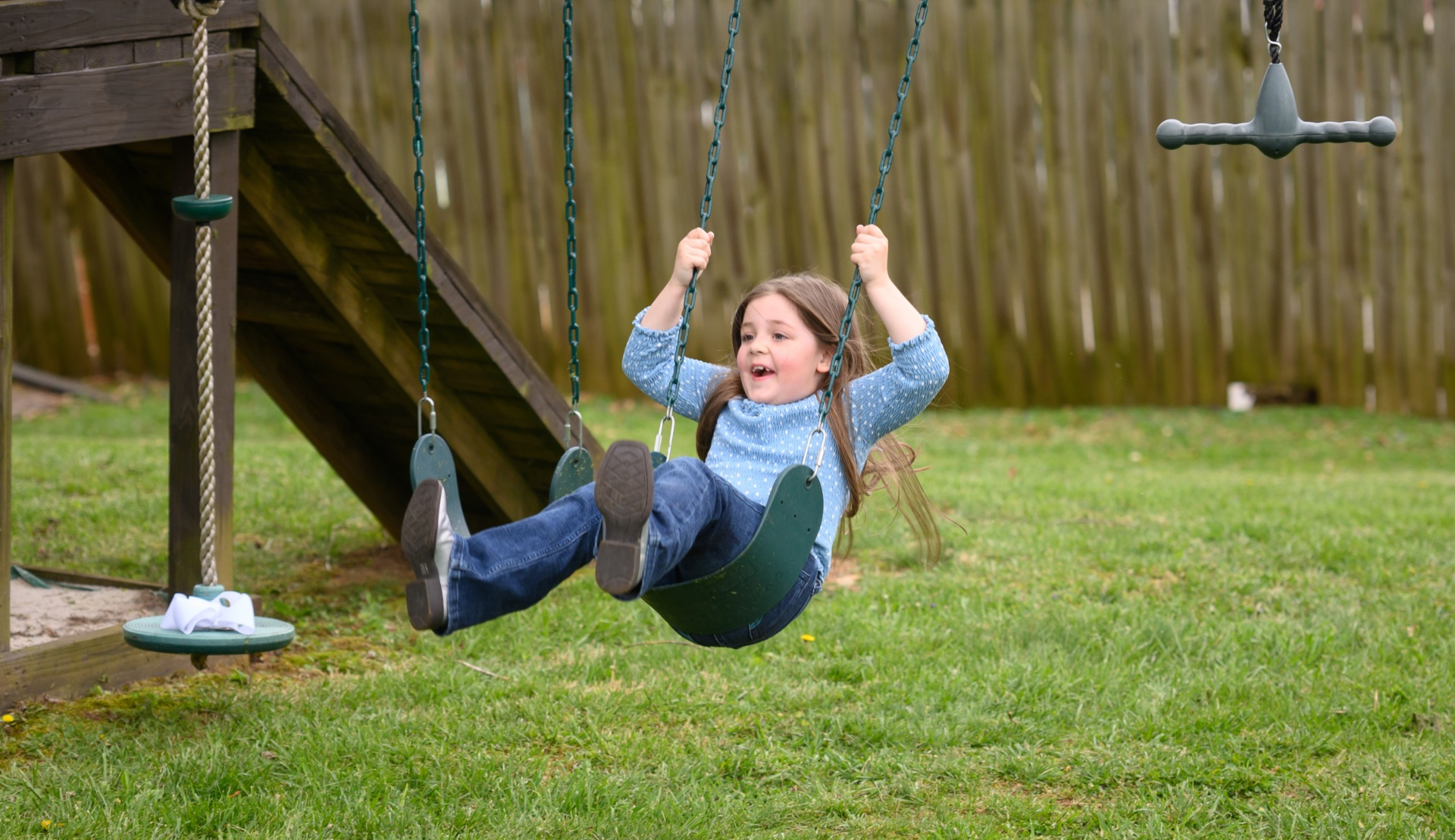 Henley smiles as she swings back and forth on a playground.