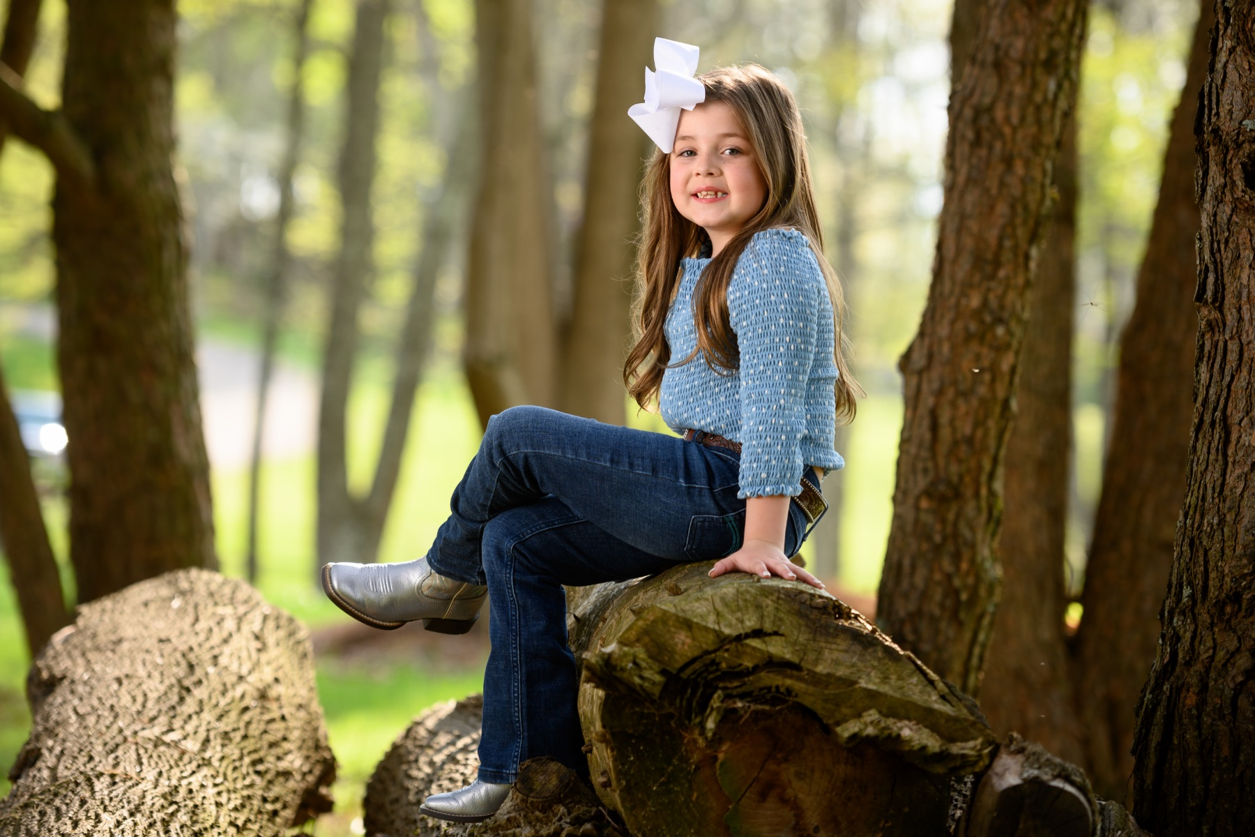 Henley Thurman, a 6-year-old white girl with brown hair, smiles as she sits on a broken tree trunk with her legs crossed. She is wearing grey boots, navy jeans, light blue top and a big white bow in her hair.