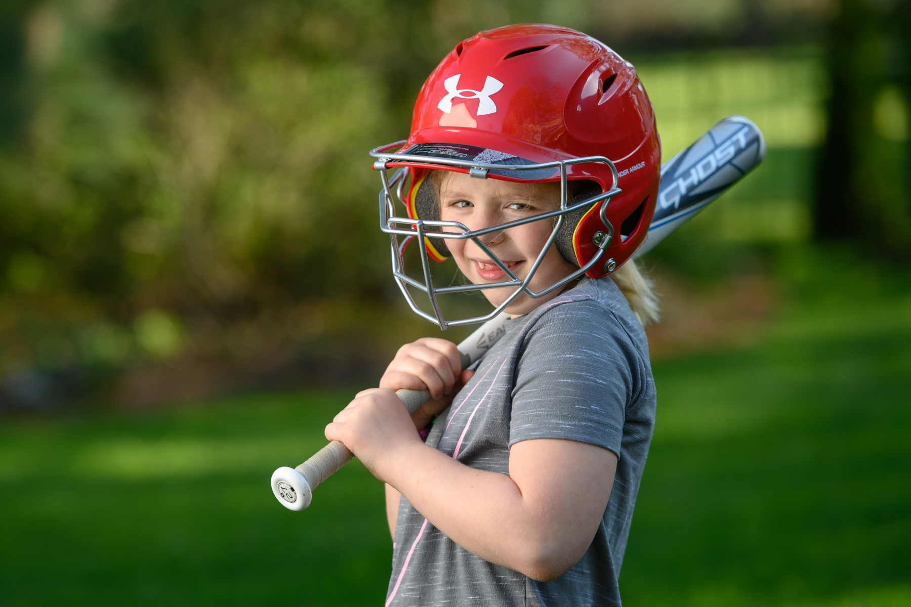 Sarah Beth Ferguson, a blonde eight-year-old white girl wearing a grey shirt, poses outside in a red softball helmet. She holds a grey bat over her shoulder.