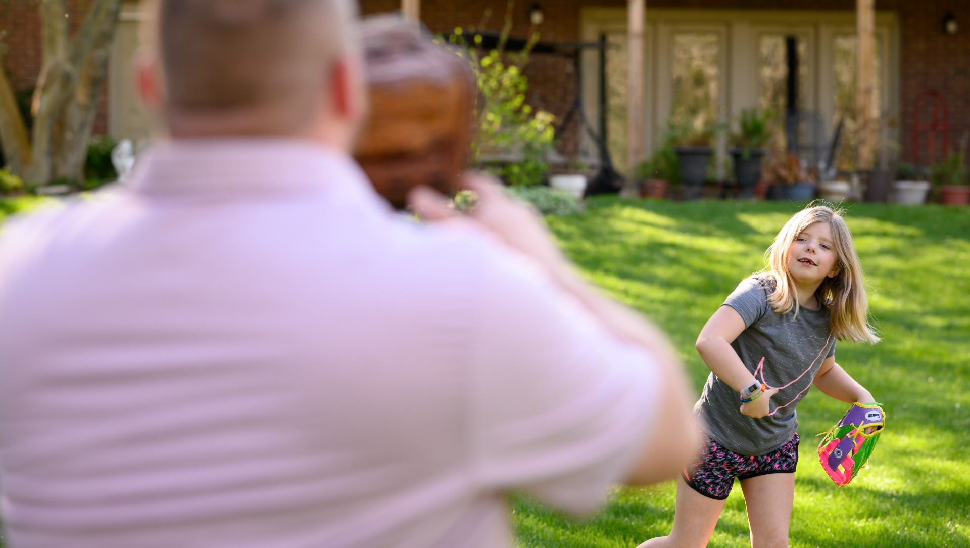 Sarah Beth throws a ball to her father, who is standing in front of the camera. She is wearing a grey shirt, black shorts with pink polka dots, and a colorful softball glove.