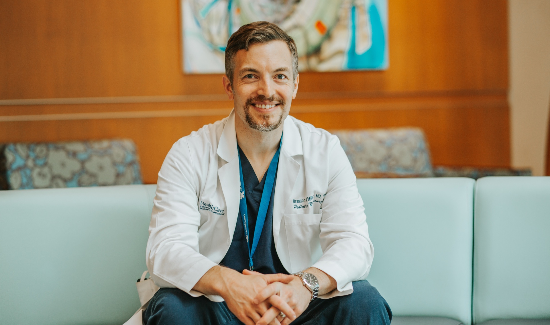 Dr. Brandon Miller, an adult white man with brown hair, sits in the lobby of UK Healthcare's Kentucky Children's Hospital, wearing a white doctor's coat and blue scrubs.