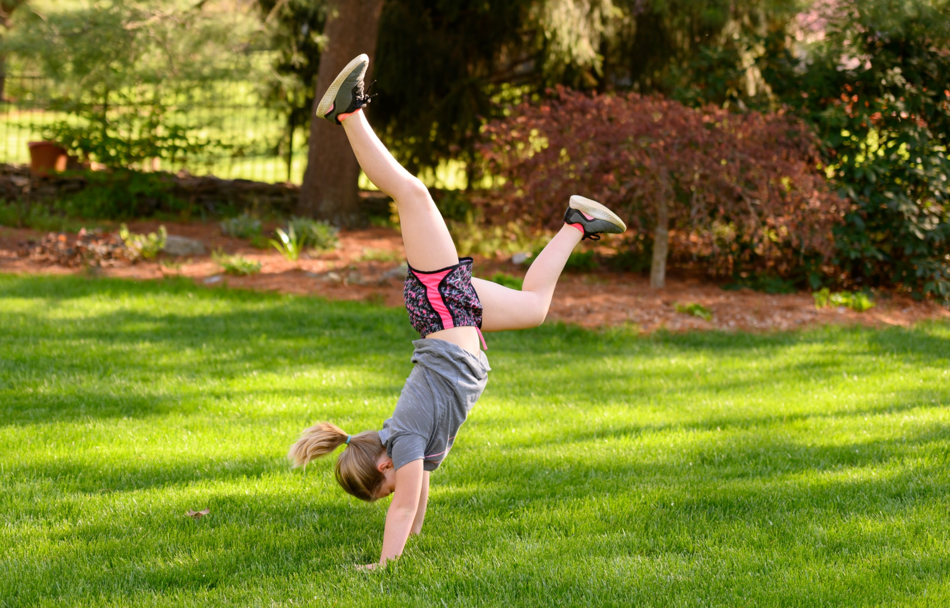 Sarah Beth does a handstand outside.