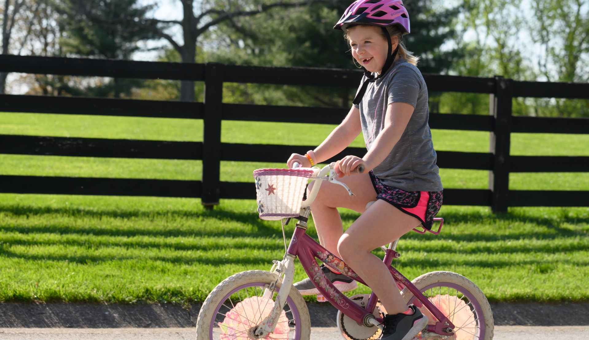 With a pink helmet on her head, Sarah Beth rides her white and pink bicycle outside.