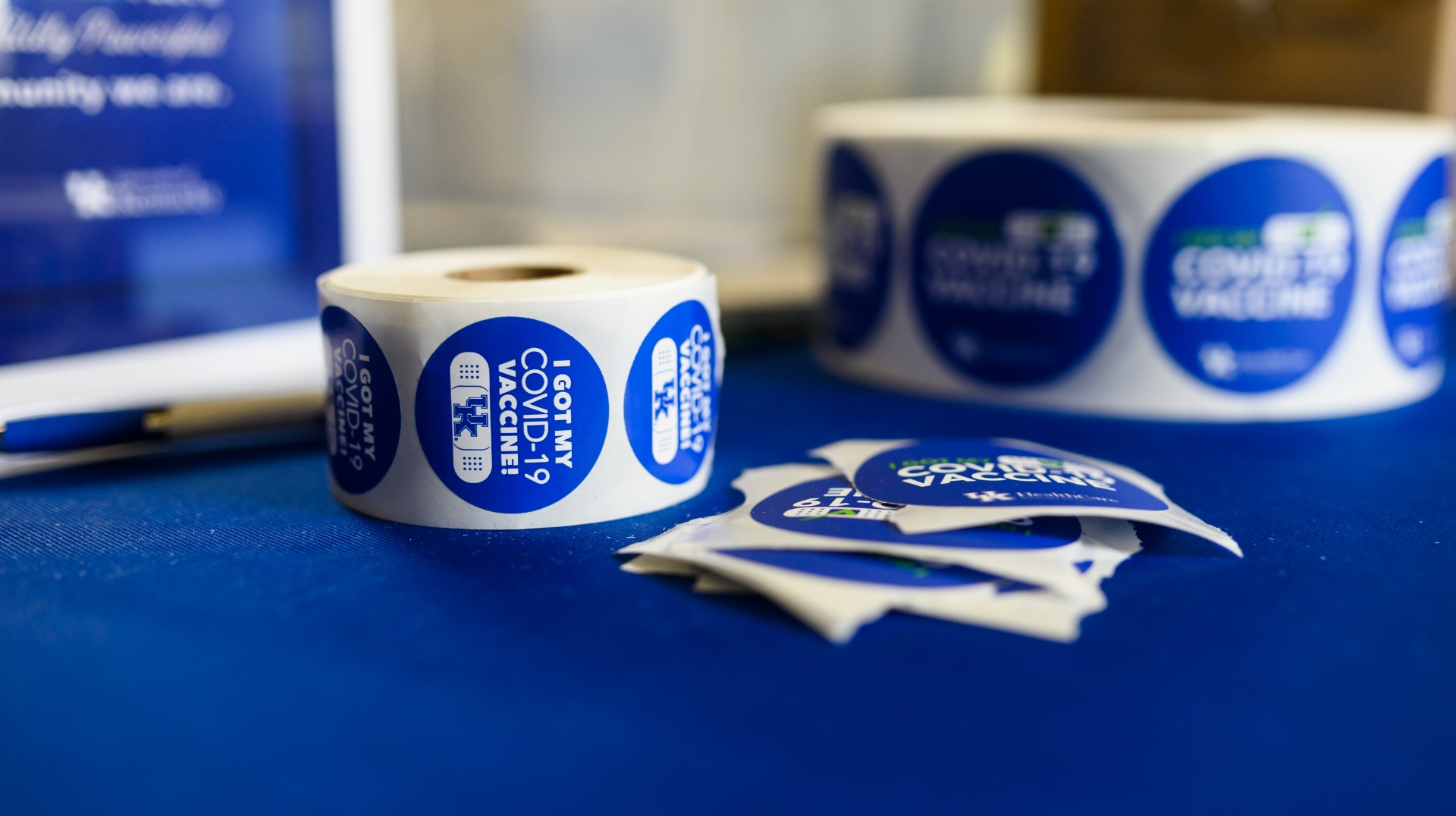 On a table are rolls of blue stickers with 'I got my COVID-19 vaccine!' printed on the front.