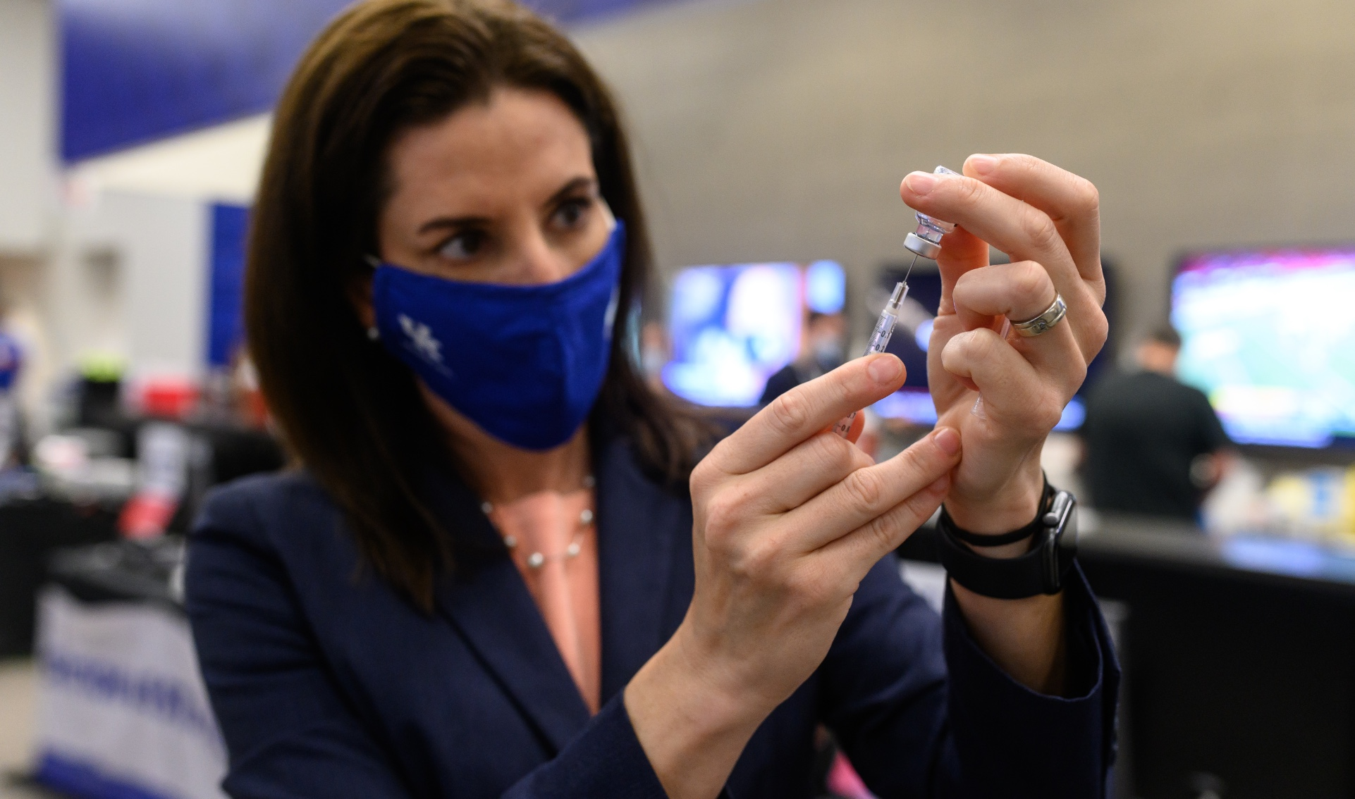 Dr. Montgomery-Yates, wearing a facemask, pulls a dose from a vial of vaccine.