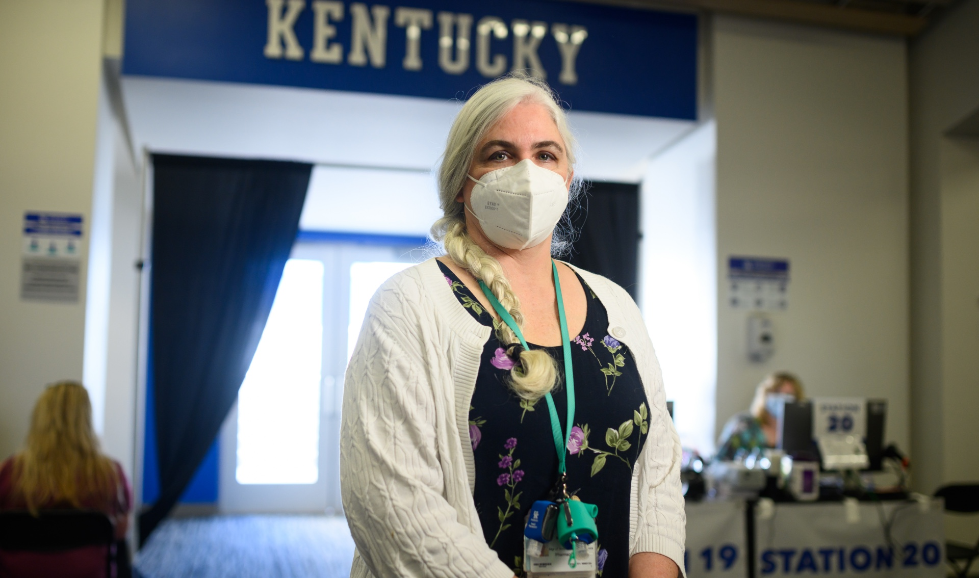 Karla Bertagnole, a middle-aged woman with long white hair in a single braid, stands inside the Kroger Field stadium. She is wearing a white facemask, a navy dress with floral designs, and a white cardigan.