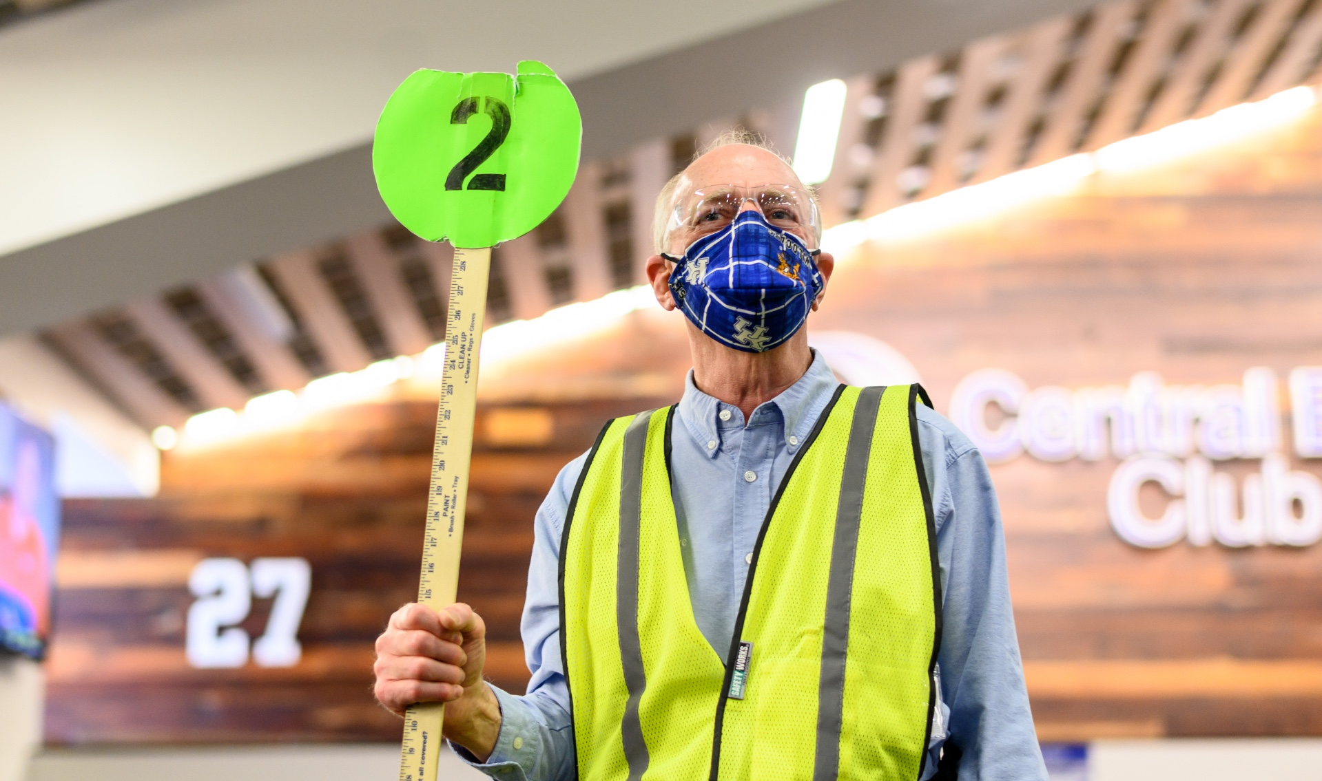 Bob Evans, an older man with grey hair, stands inside the Kroger Field stadium directing people. He is wearing a blue facemask, a green reflective vest, a blue shirt, and is and holding up a number 2 sign.